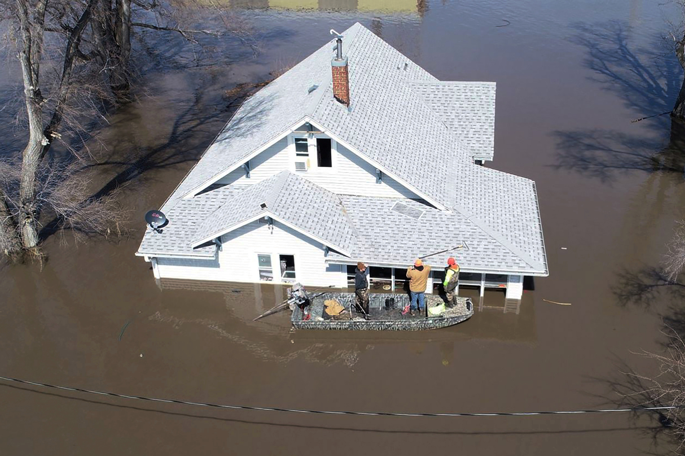 Lanni Bailey and a team from Muddy Paws Second Chance Rescue enter a flooded house to pull out several cats during the flooding of the Missouri River near Glenwood, Iowa, March 18, 2019.