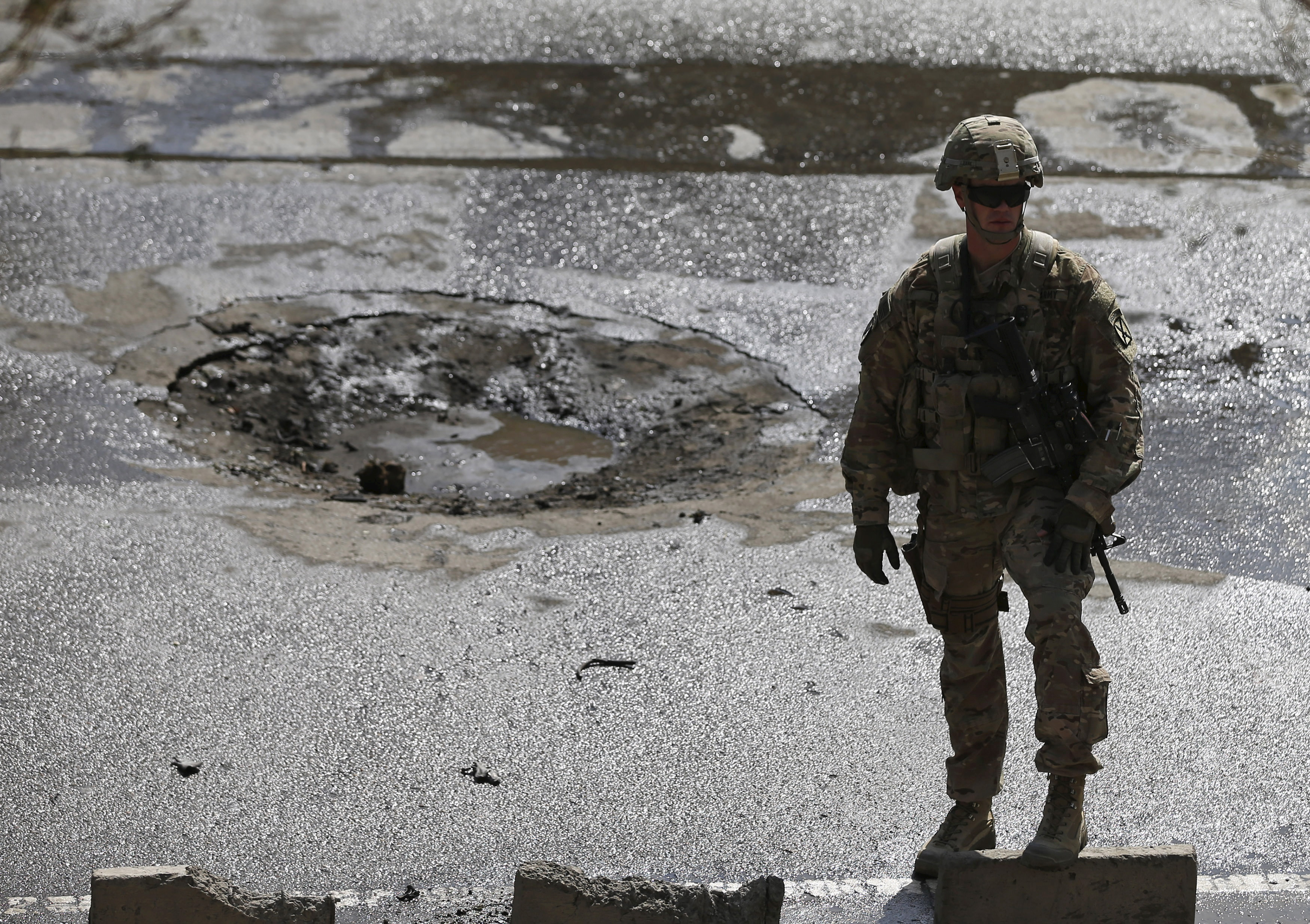 A NATO soldier stands at the site of a suicide car bomb blast in Kabul, Afghanistan, Oct. 11, 2015.