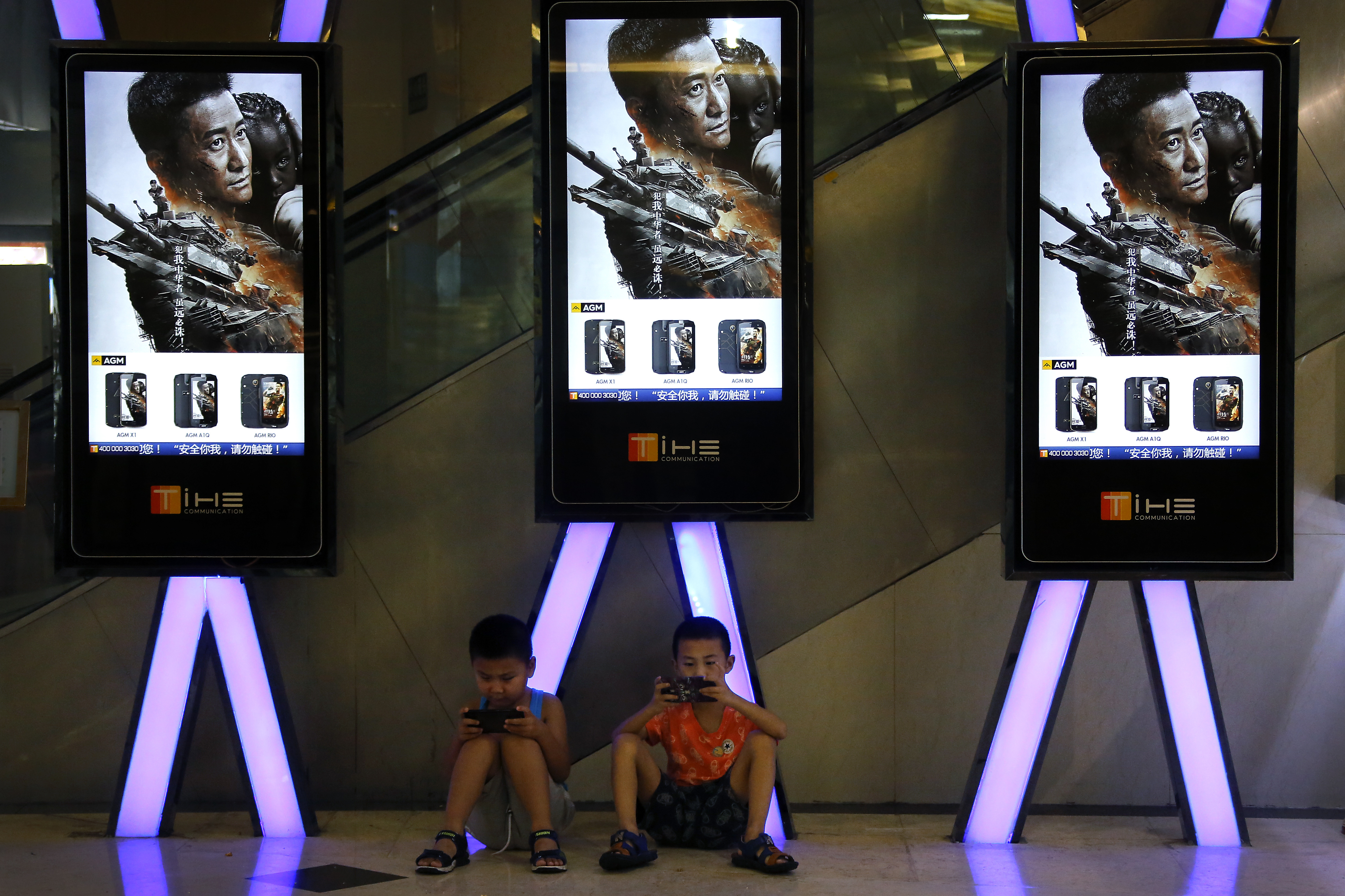 """Children use smartphones near monitors displaying a Chinese action movie """"Wolf Warrior 2"""" at a cinema in Beijing, Aug. 10, 2017. The patriotic film reportedly inspired by evacuations of Chinese civilians in Libya and Yemen is becoming one of China's ..."""