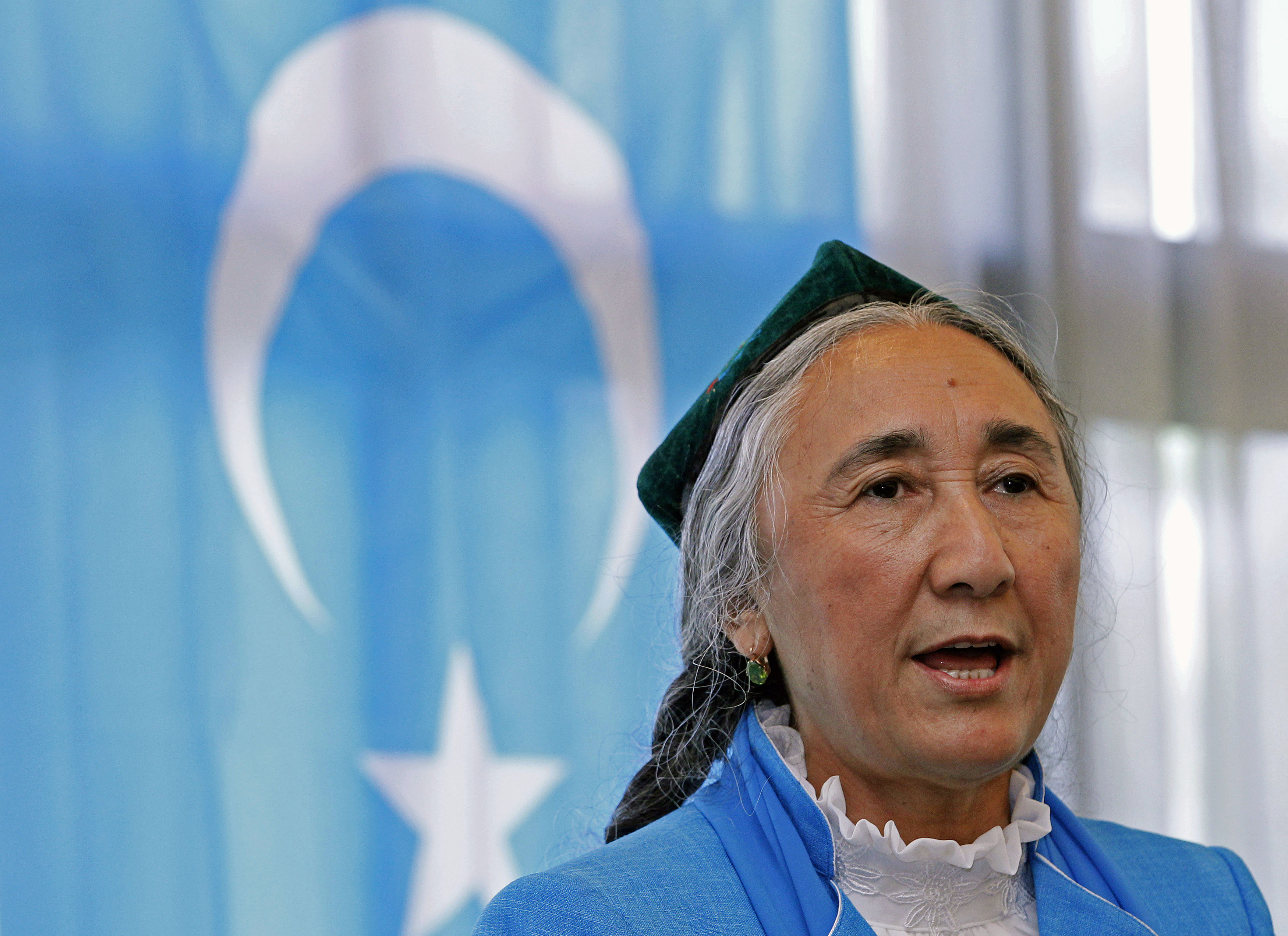 Uighur leader Rebiya Kadeer delivers a speech in front of a East Turkestan flag at the fourth General Assembly of the World Uighur Congress in Tokyo, May 14, 2012.