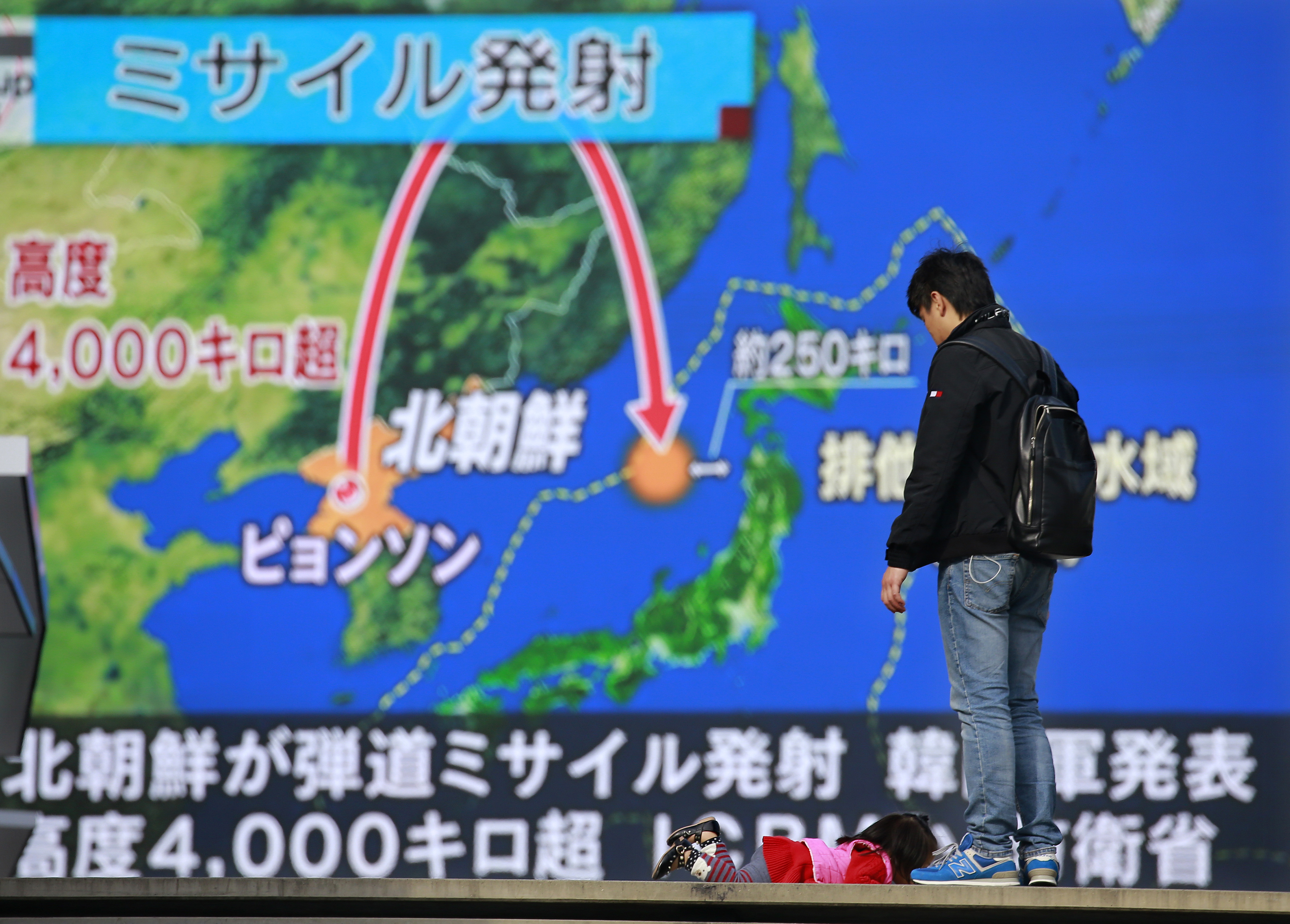 A man stands in front of a huge screen showing TV news program reporting North Korea's missile launch, in Tokyo, Nov. 29, 2017.