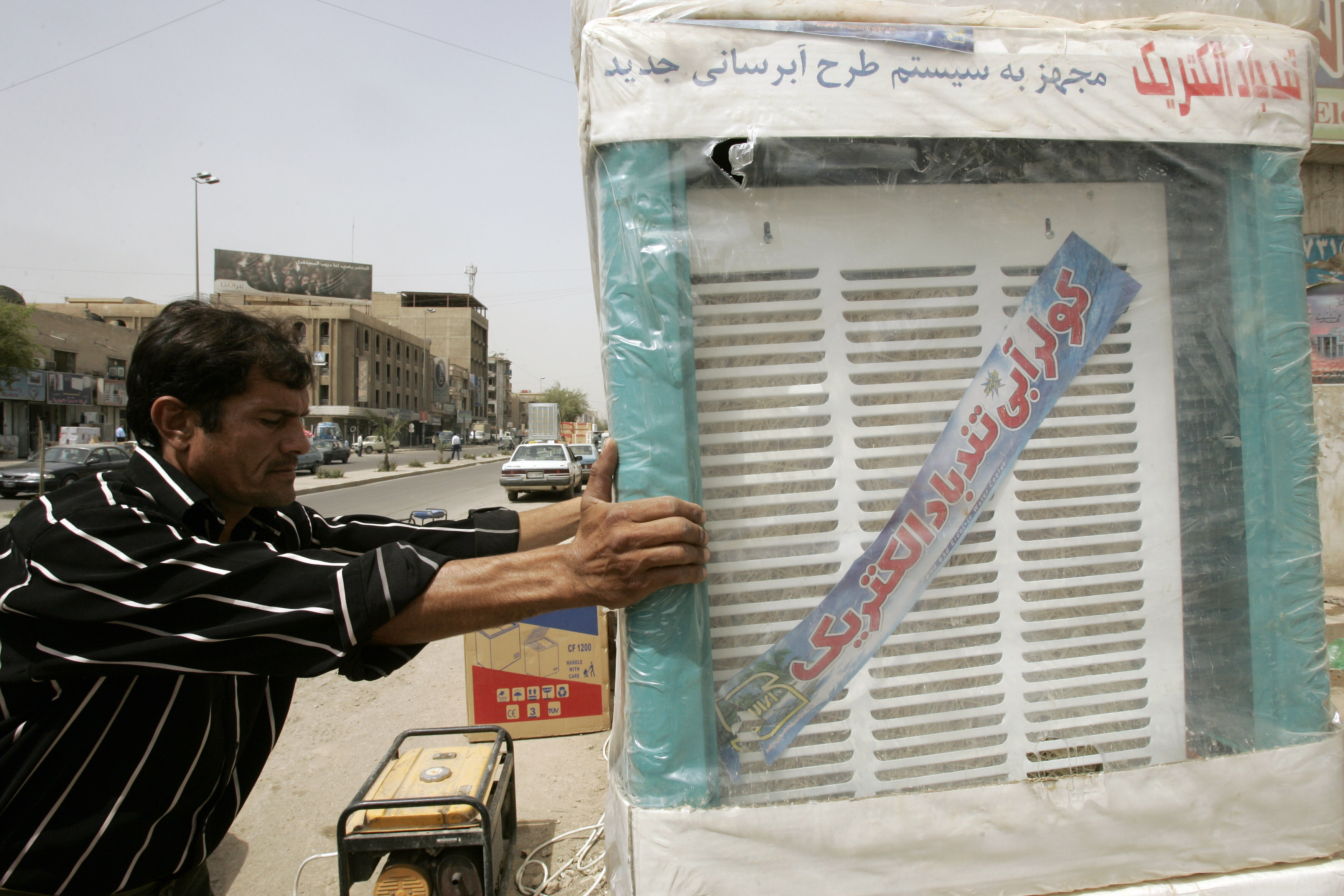 FILE - An Iraqi merchant receives a delivery of Iranian-made air coolers, at his shop in central Baghdad.