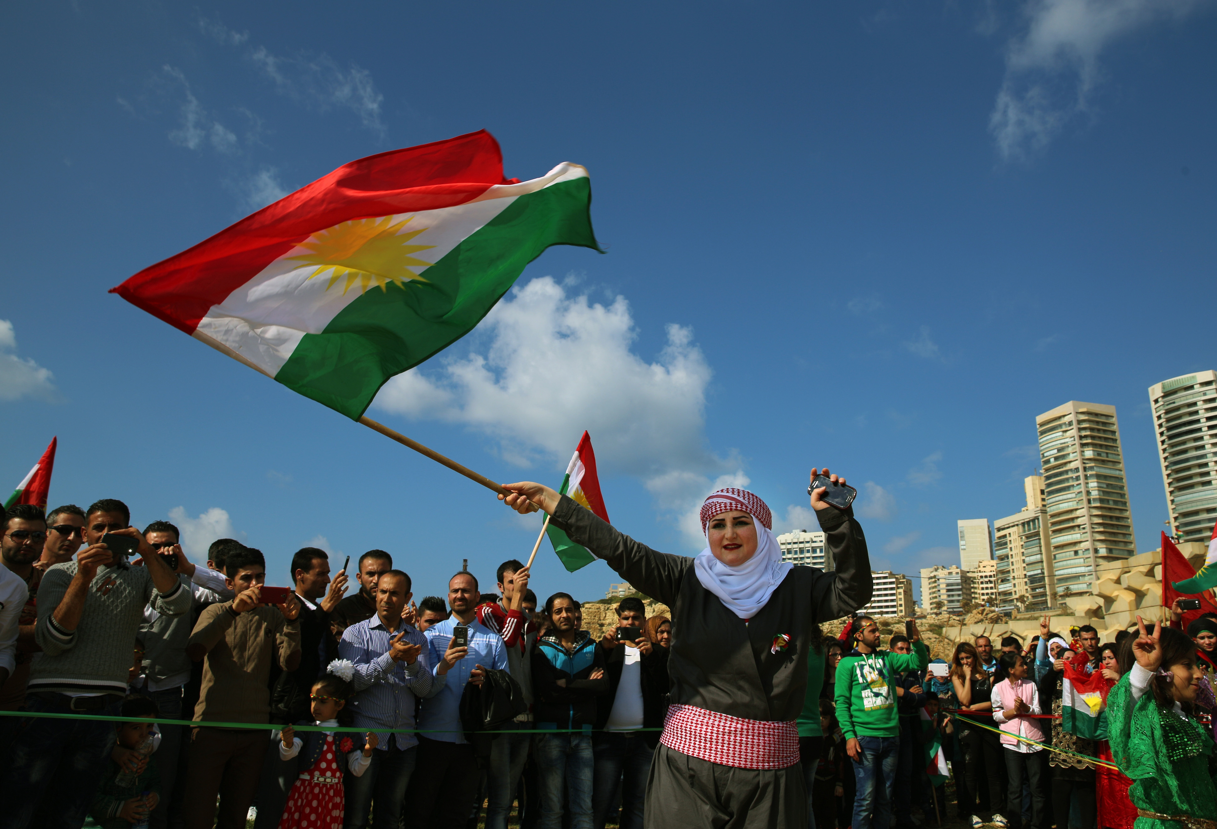 Syrian Kurd Nazdan, who fled her home in Qamishli, Syria, wears traditional clothes as she dances and waves a Kurdish flag, during a celebration of Nowruz day, in Beirut, Lebanon, Mar. 21, 2016.