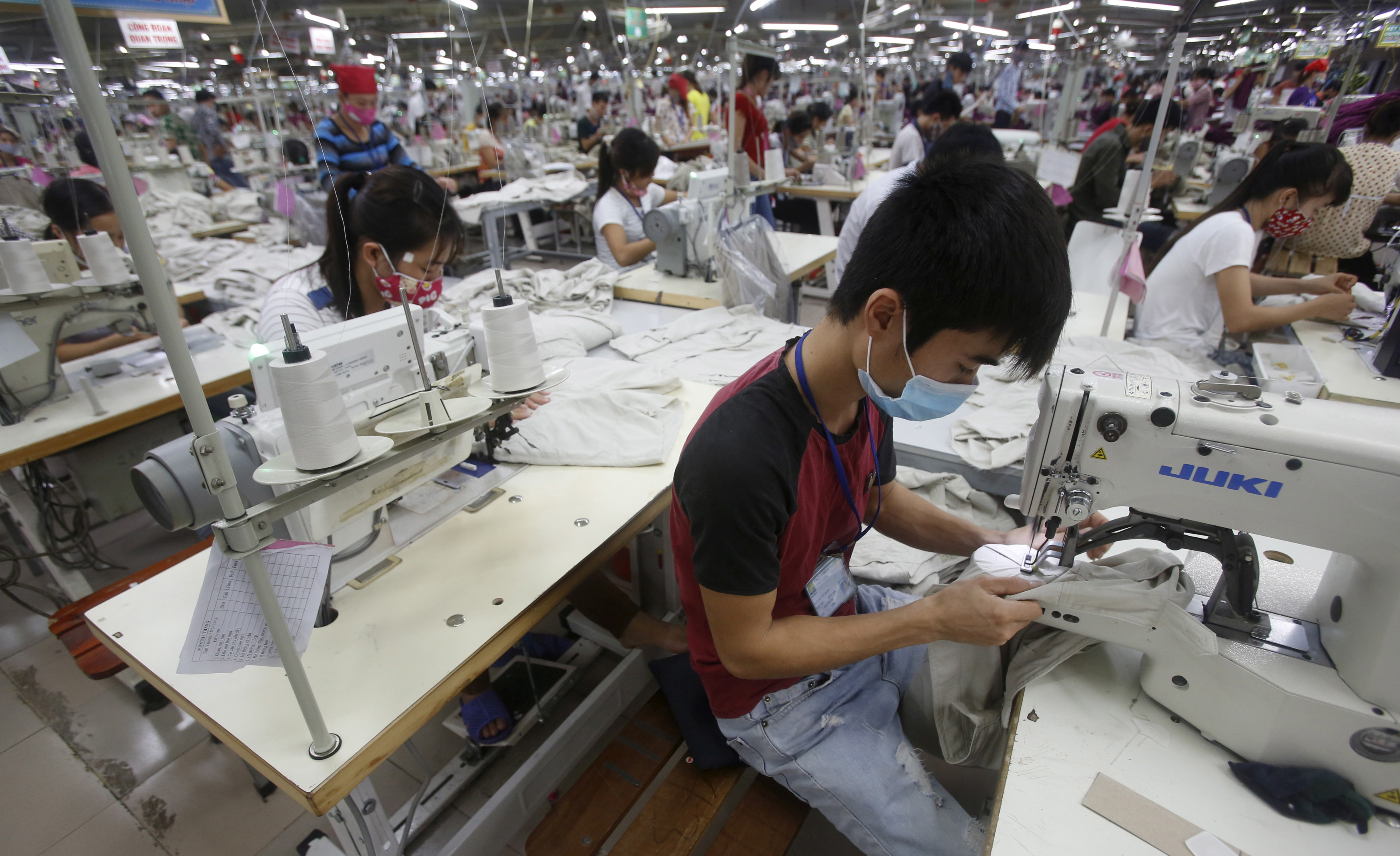 Laborers work at a garment factory in Bac Giang province, near Hanoi, Vietnam, Oct. 21, 2015.