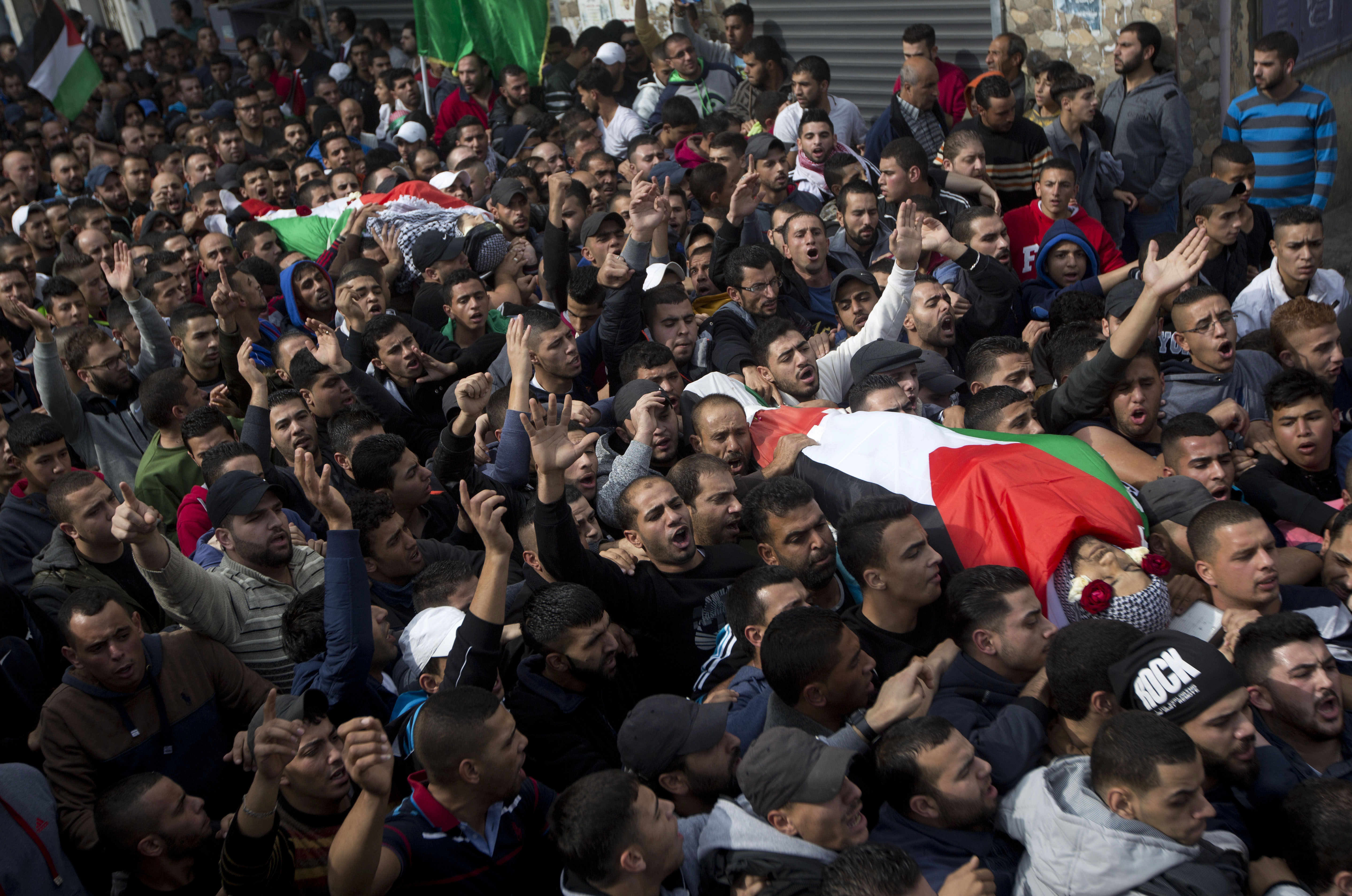 Palestinians carry the bodies of Ahmed Abu al-Aish, 28, and Laith Manasrah, 21, during their funeral in the Qalandia refugee camp on the outskirts of the West Bank city of Ramallah, Monday, Nov. 16, 2015.