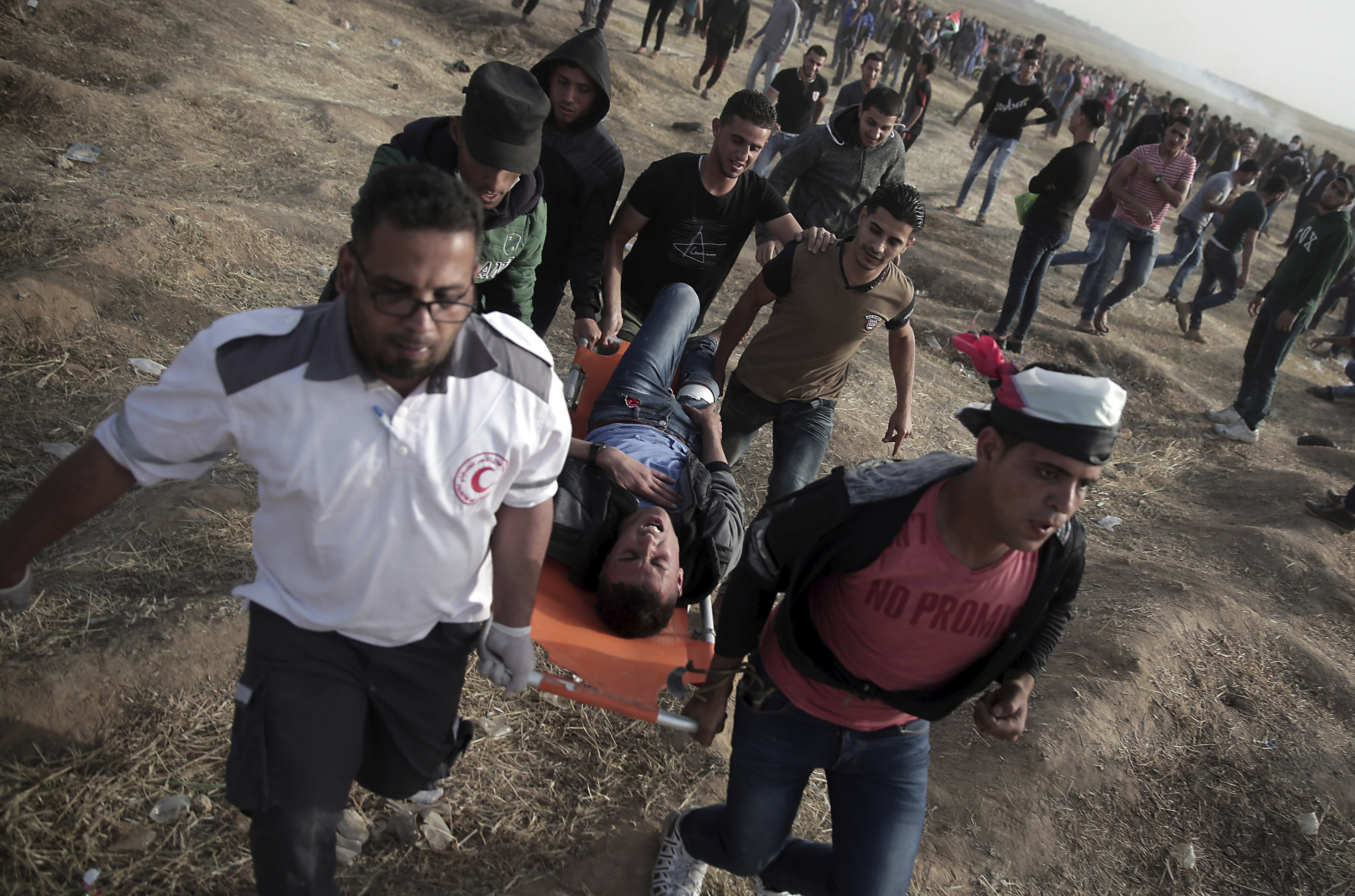 Palestinian protesters evacuate a wounded man during a protest at the Gaza Strip's border with Israel, April 13, 2018.