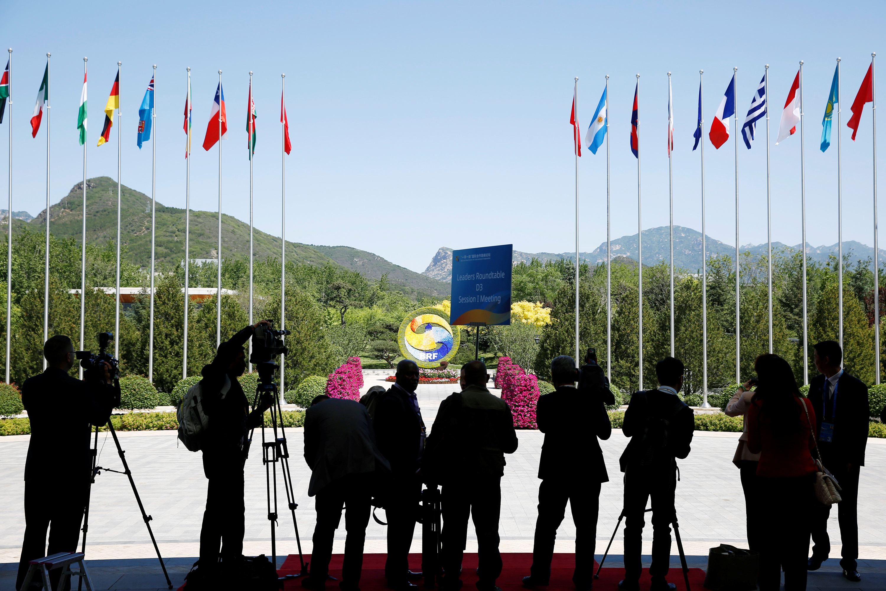 FILE - Journalist take pictures outside the venue of a summit at the Belt and Road Forum in Beijing, China, May 15, 2017.