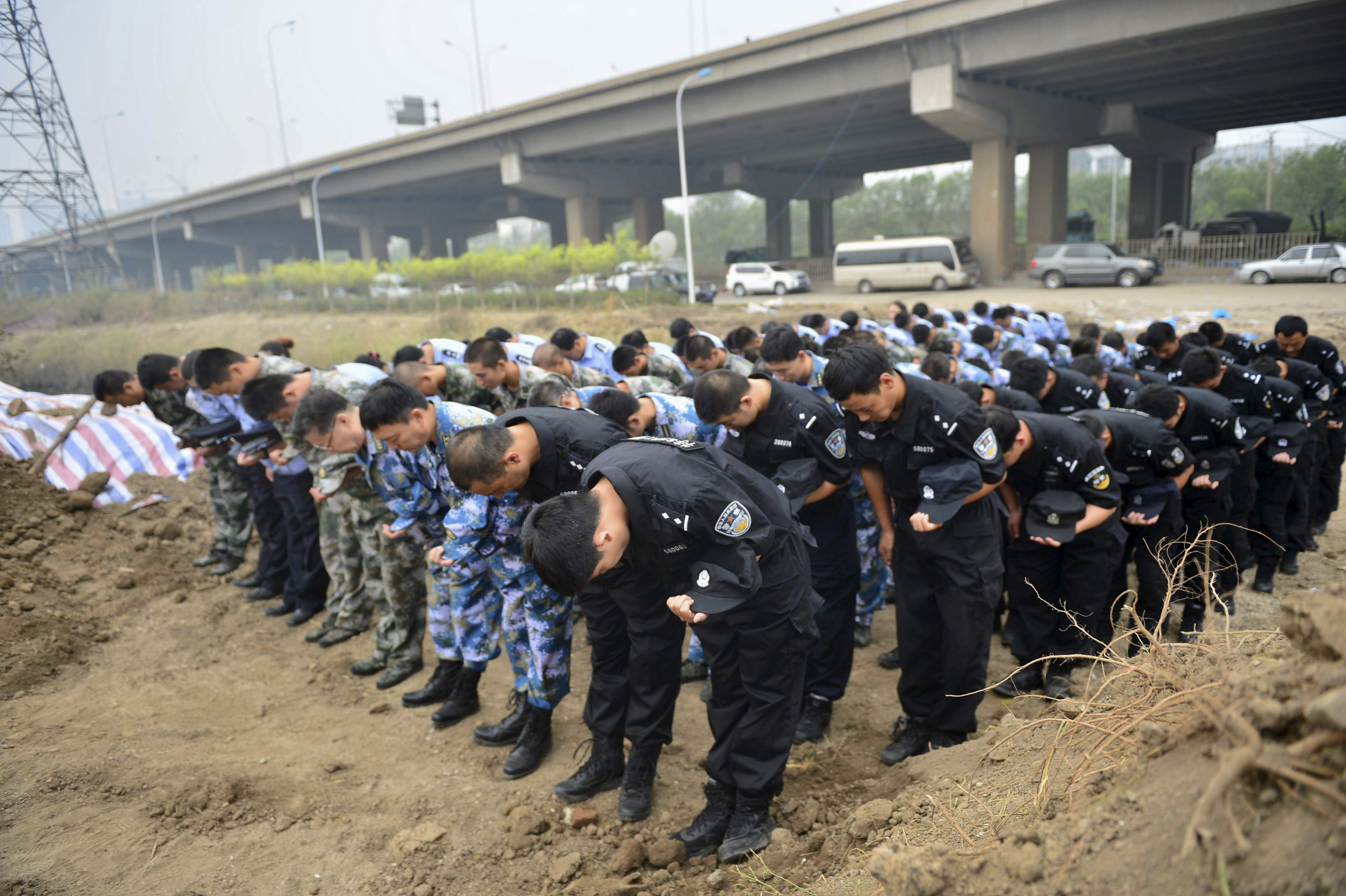 Representatives from the police and People's Liberation Army (PLA), marking the seventh day since the Tianjin explosions, pay tribute to the people who died, in a ceremony at Binhai new district, Tianjin, China, Aug. 18, 2015.