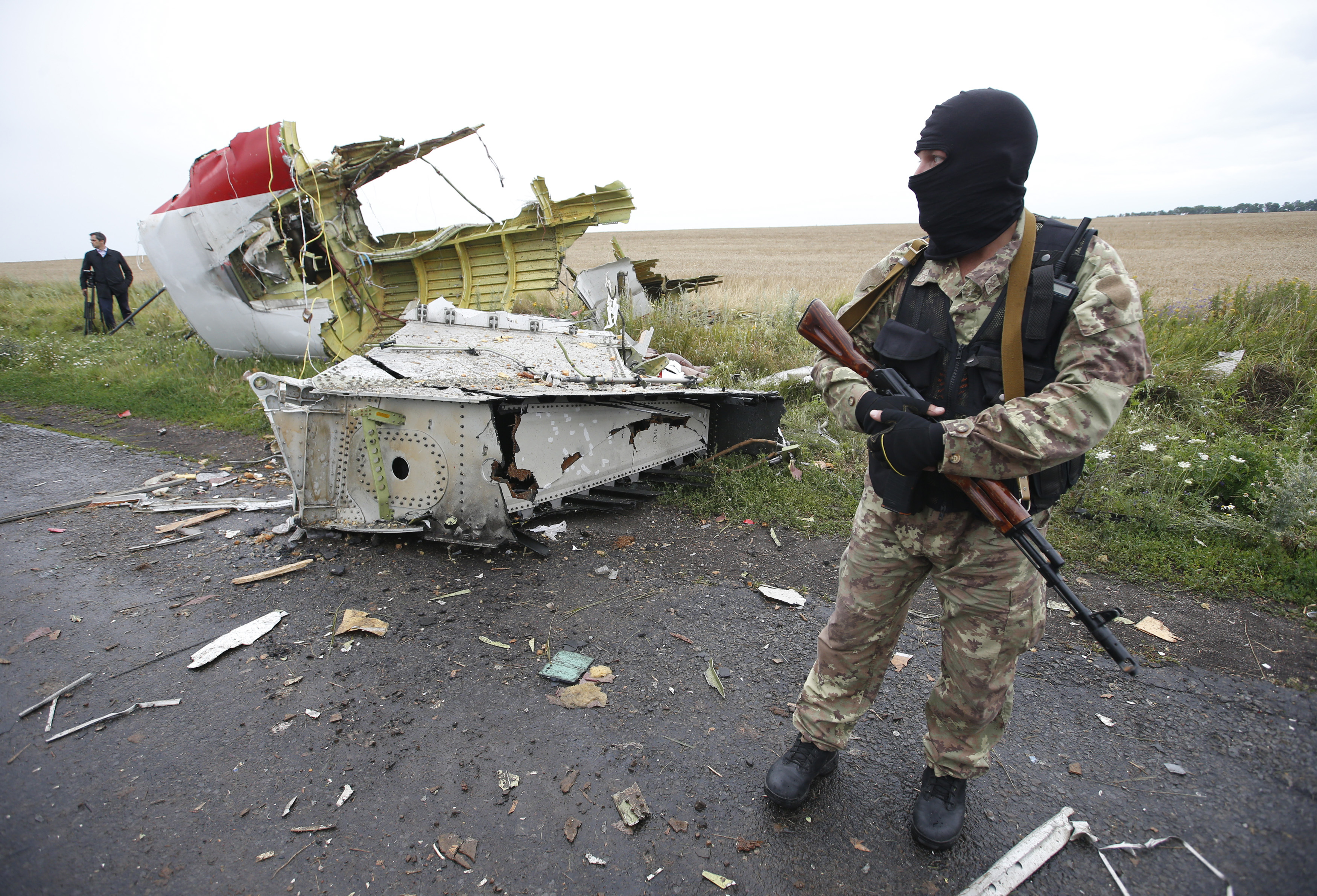 A pro-Russian separatist stands at the crash site of Malaysia Airlines flight MH17, near the settlement of Grabovo in the Donetsk region, July 18, 2014.