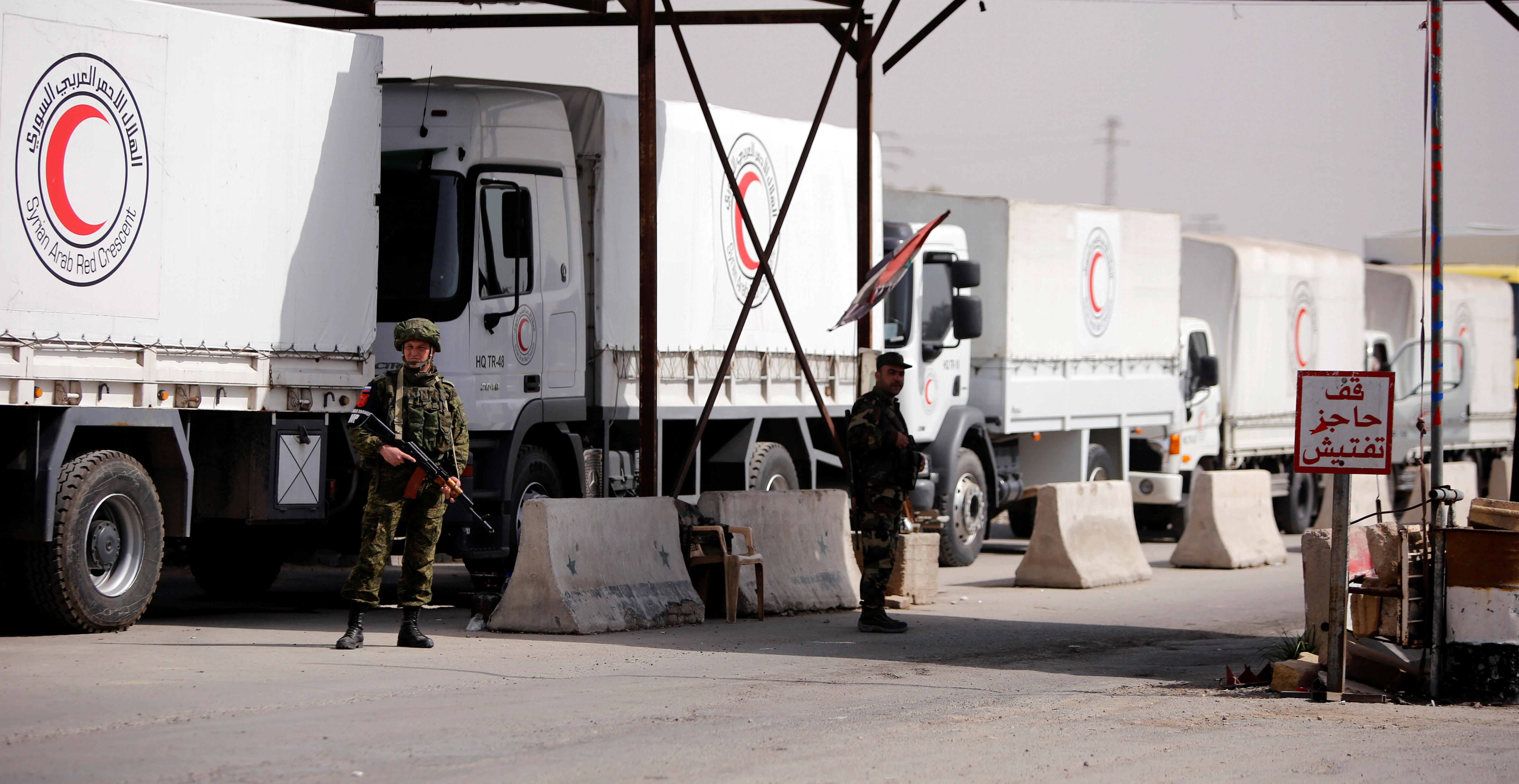 Russian soldiers are seen securing Syrian Arab Red Crescent trucks carrying aid at a checkpoint near Wafideen camp in Damascus, March 5, 2018.