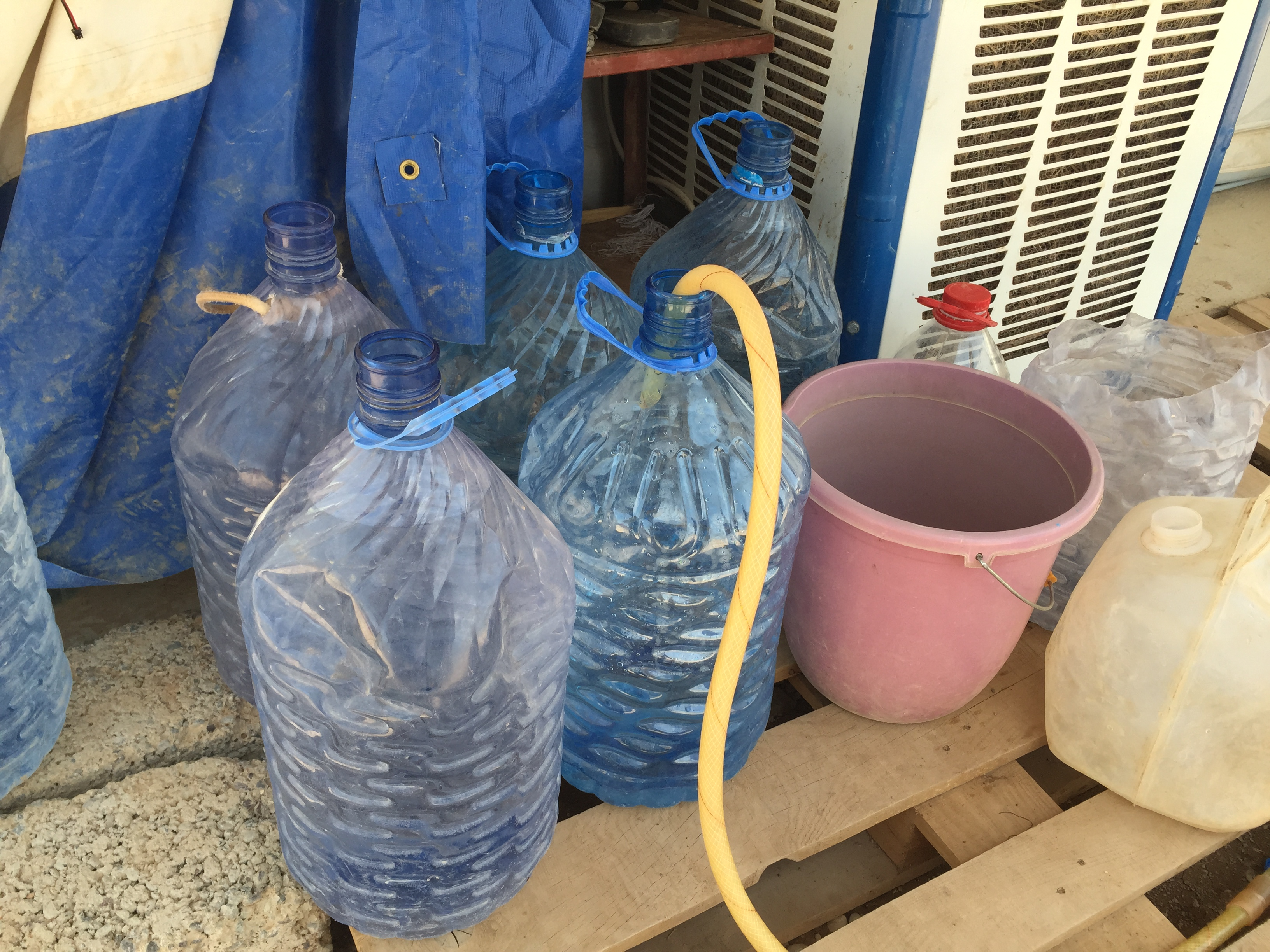 "Filling up water bottles in the Baharka camp on the outskirts of Irbil, in the Kurdistan region of Iraq. Considered a ""five-star"" camp, Baharka houses some 4,000 people, half of whom are teenagers, Aug 5, 2015 (VOA photo - Sharon Behn)."