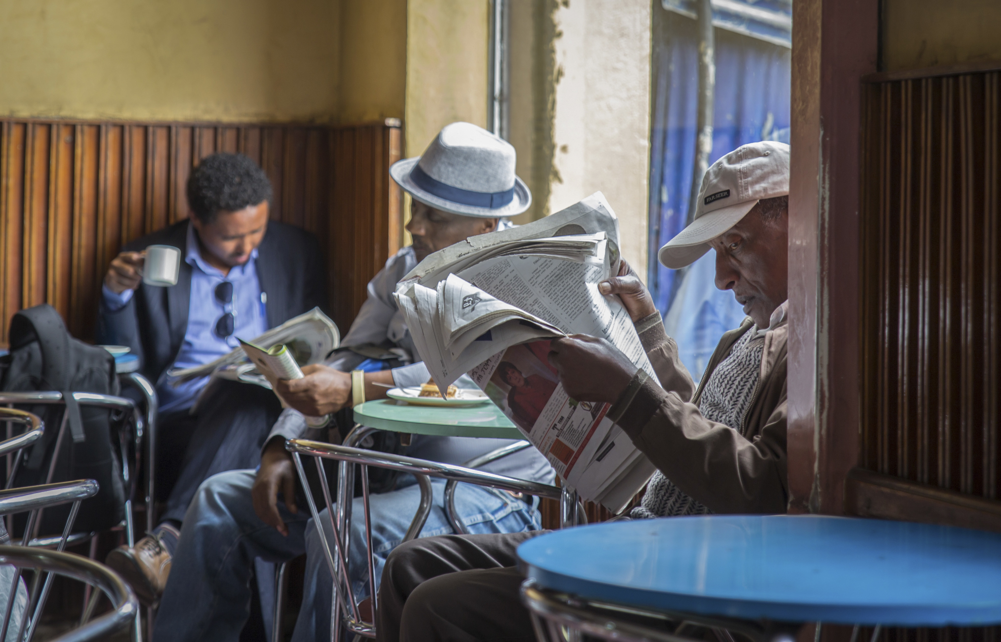 Ethiopian men read newspapers and drink coffee at a cafe in Addis Ababa, Ethiopia Monday, Oct. 10, 2016.