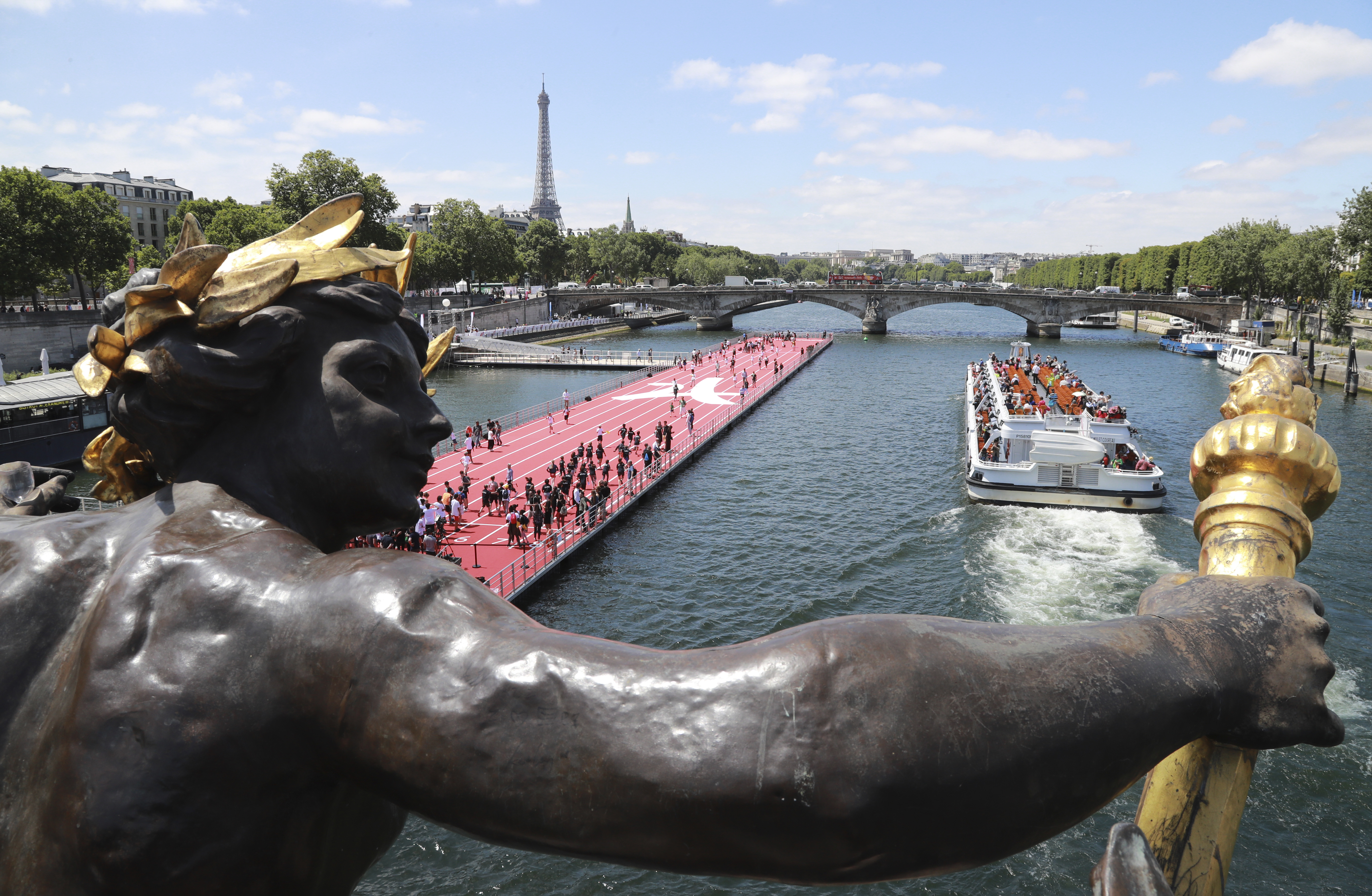 A photo taken from the bridge Alexandre III shows an athletics track installed on the river Seine with a tour boat passing by during a bid to promote the candidacy of the city of Paris for the 2024 Summer Olympics Games, June 23, 2017.