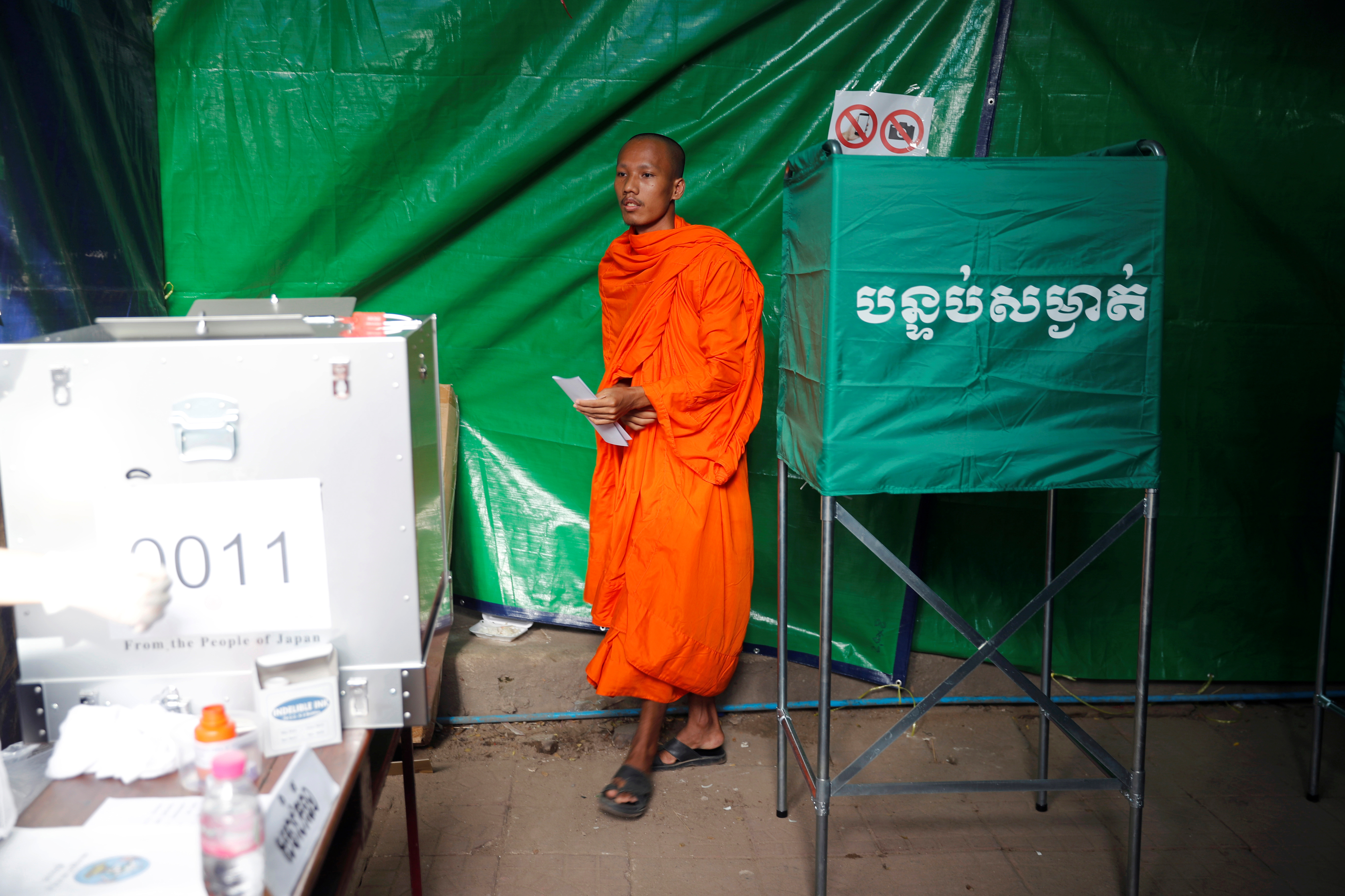 A monk votes at a polling station during a general election in Phnom Penh, Cambodia, July 29, 2018.