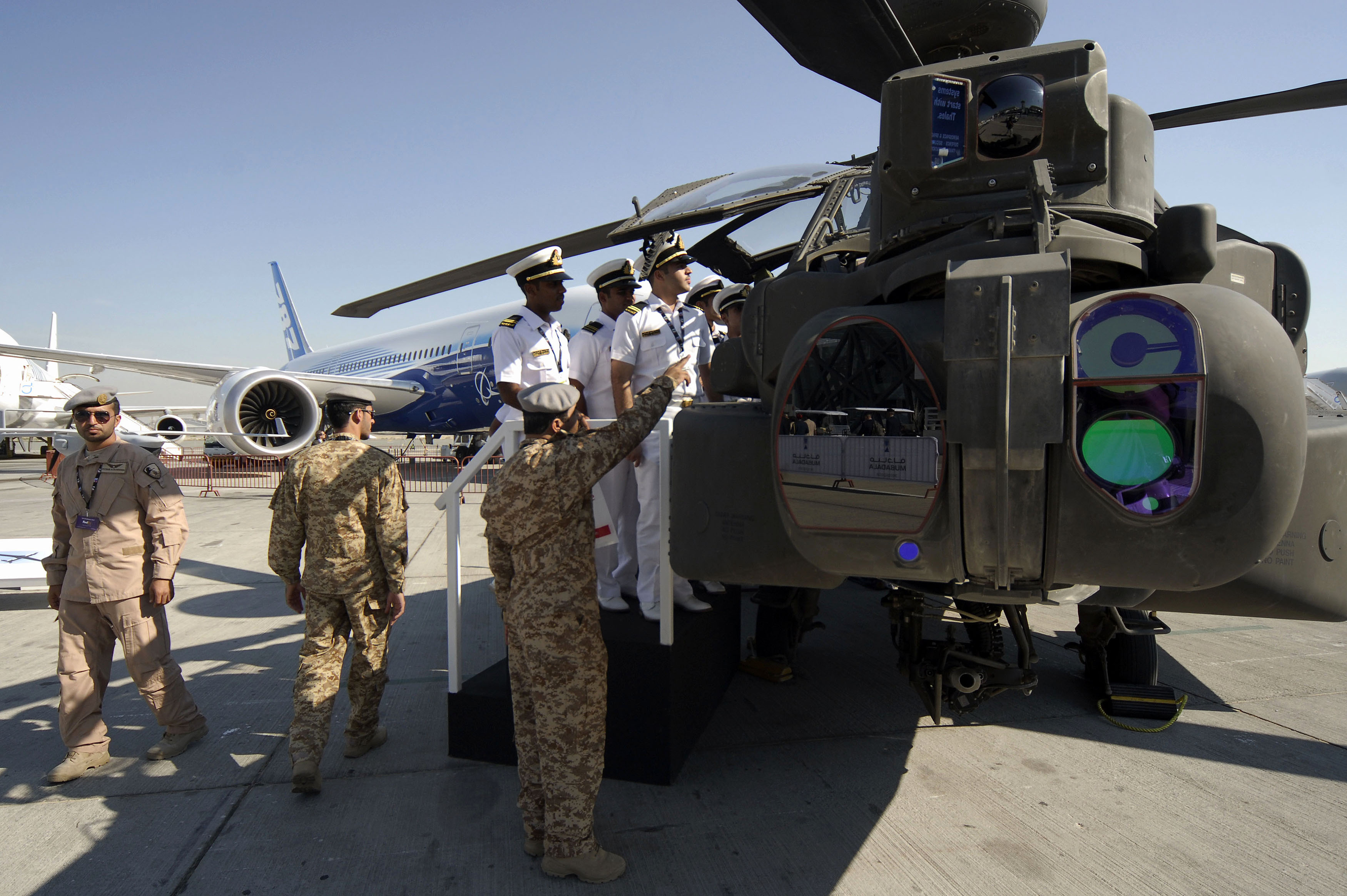 FILE - Visitors look at a AH-64D Apache helicopter during an airshow in Dubai, UAE.