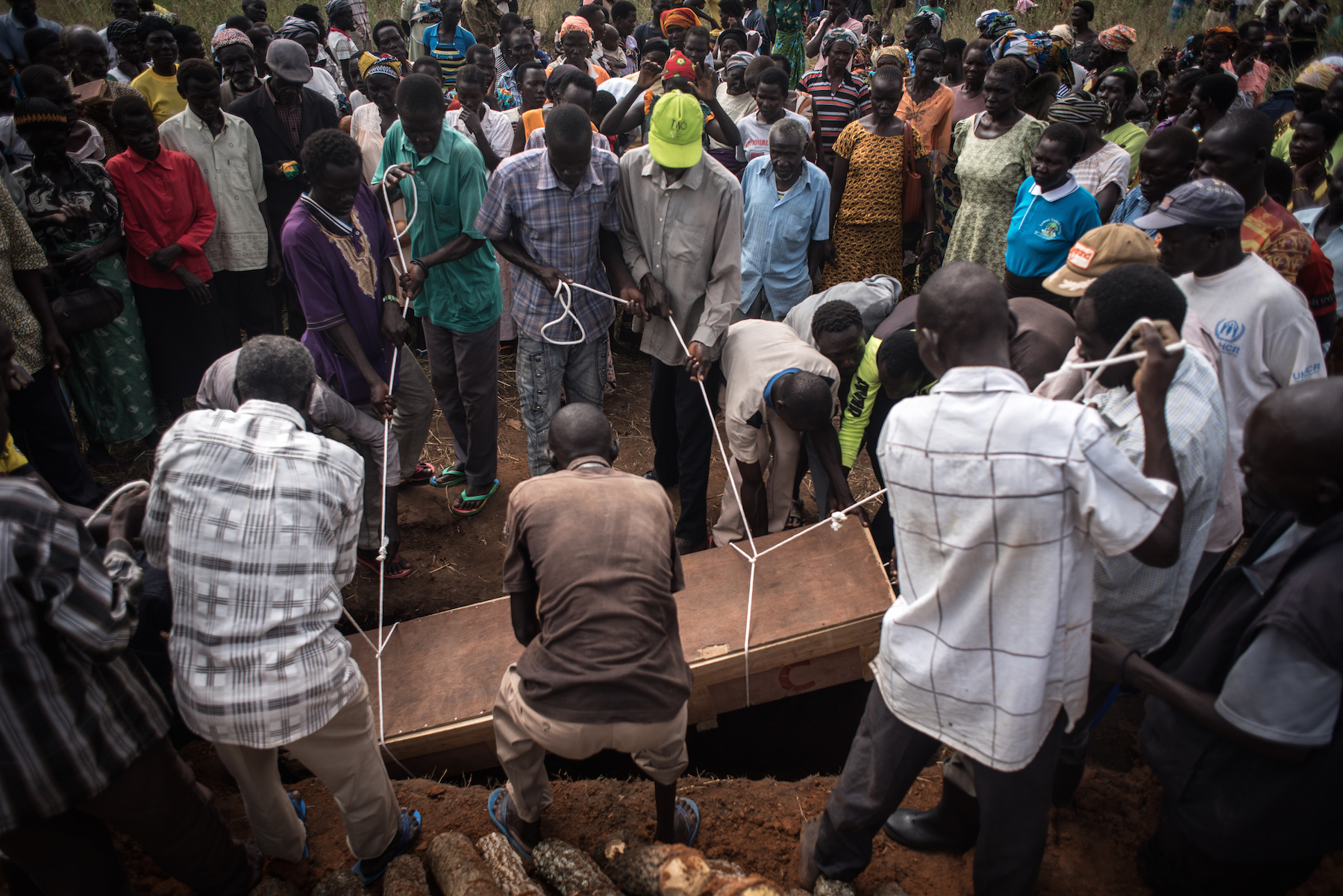 The casket containing the body of Duku Evans, who was killed November 3 amid fighting between government troops and rebels in Logo displaced persons camp in Kajo Keji, South Sudan, is lowered into a grave on the Ugandan border, Nov. 5, 2017.