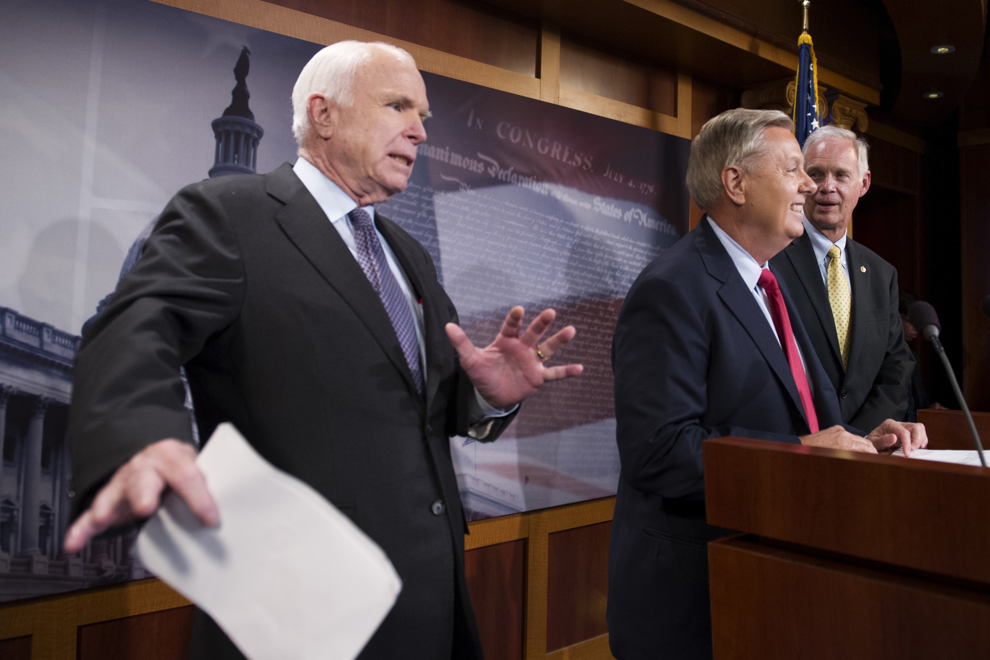 FILE - In this July 27, 2017, photo, Sen. John McCain, R-Ariz., left, jokes around as he and Lindsey Graham, R-S.C., center, and Sen. Ron Johnson, R-Wis., speak to reporters at the Capitol in Washington.