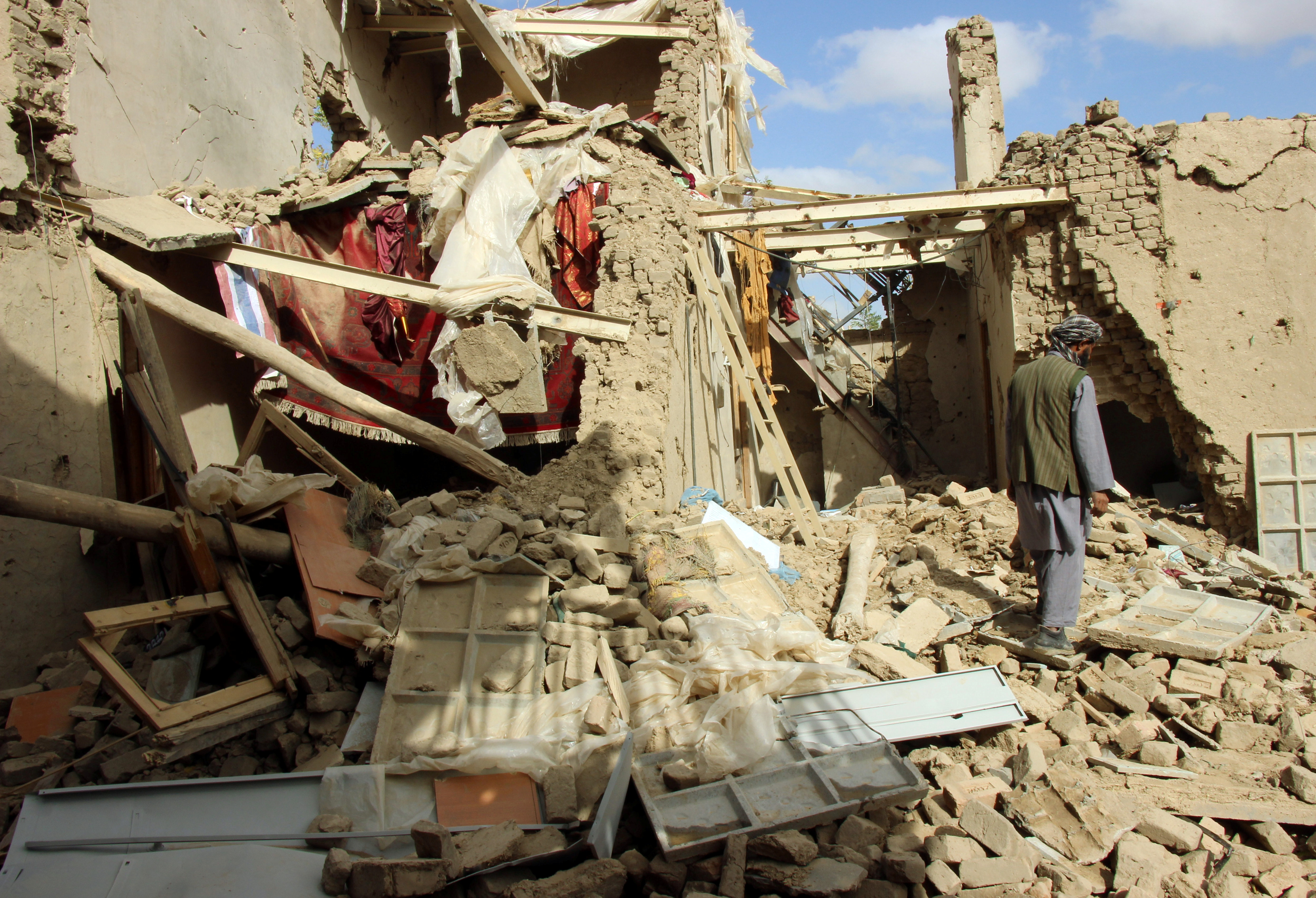 FILE - An Afghan man inspects a house destroyed during an air strike called in to protect Afghan and U.S. forces during a raid on suspected Taliban militants, in Kunduz, Afghanistan, Nov. 4, 2016.