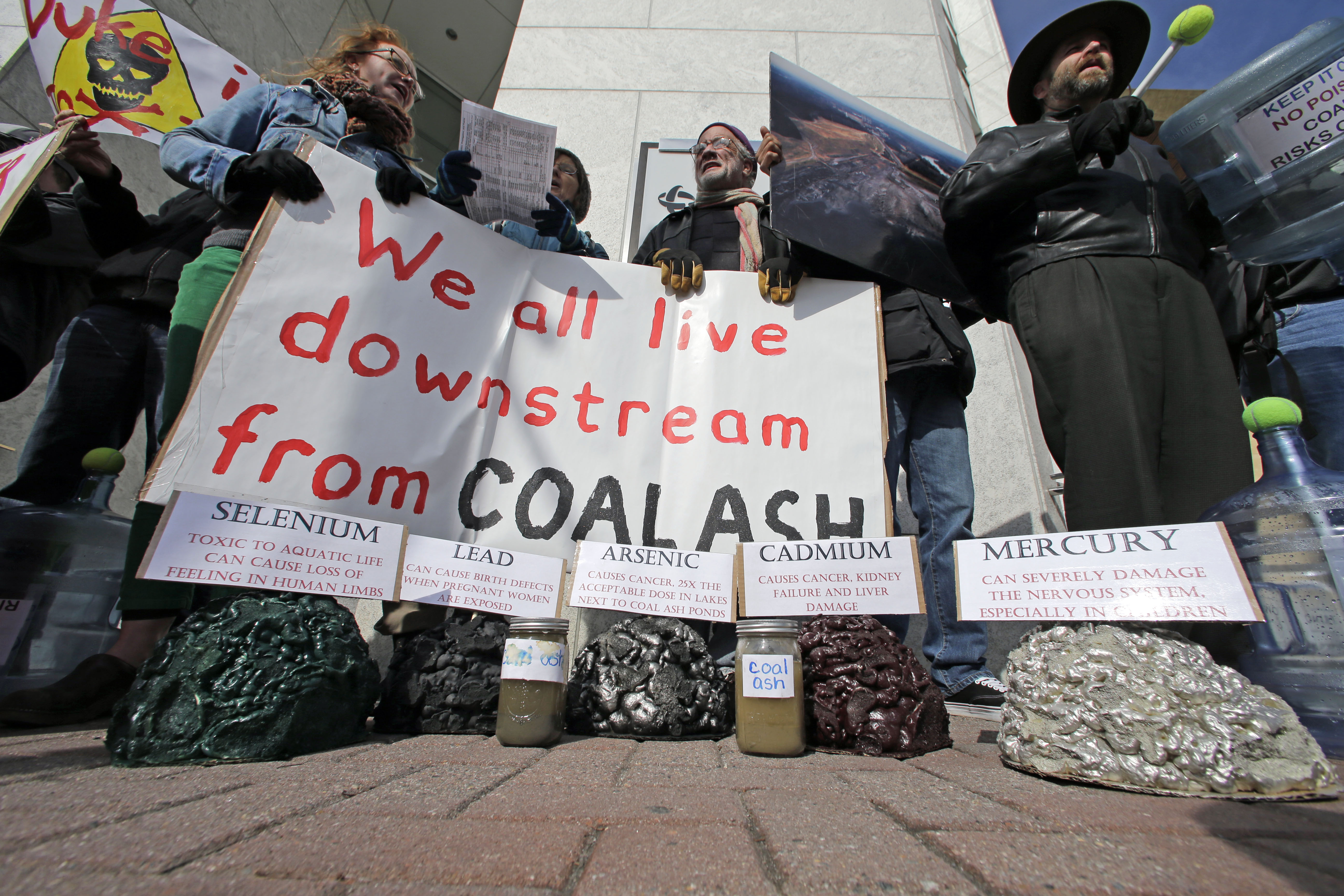 FILE - Demonstrators chant and hold signs behind a display of coal ash and the heavy metals in it during a protest near Duke Energy's headquarters in Charlotte, N.C., Feb. 6, 2014 over Duke Energy's coal plants.