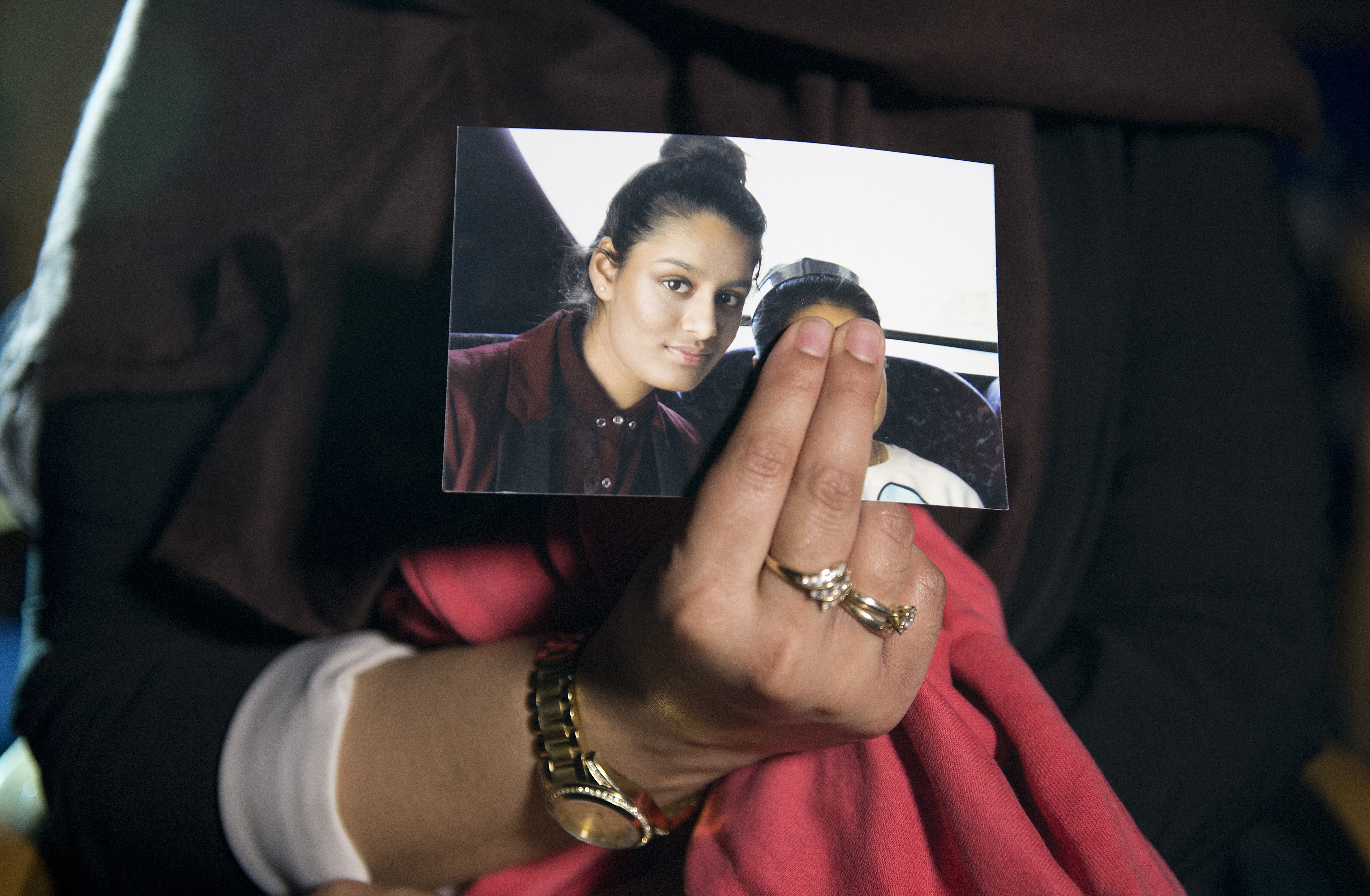 FILE - A picture of Shamima Begum is held by her sister, who was being interviewed by reporters in central London, Feb. 22, 2015. Britain last week revoked nationality of ShamimaBegum, a 19-year-old woman of Bangladeshi heritage who joined IS in Sy...