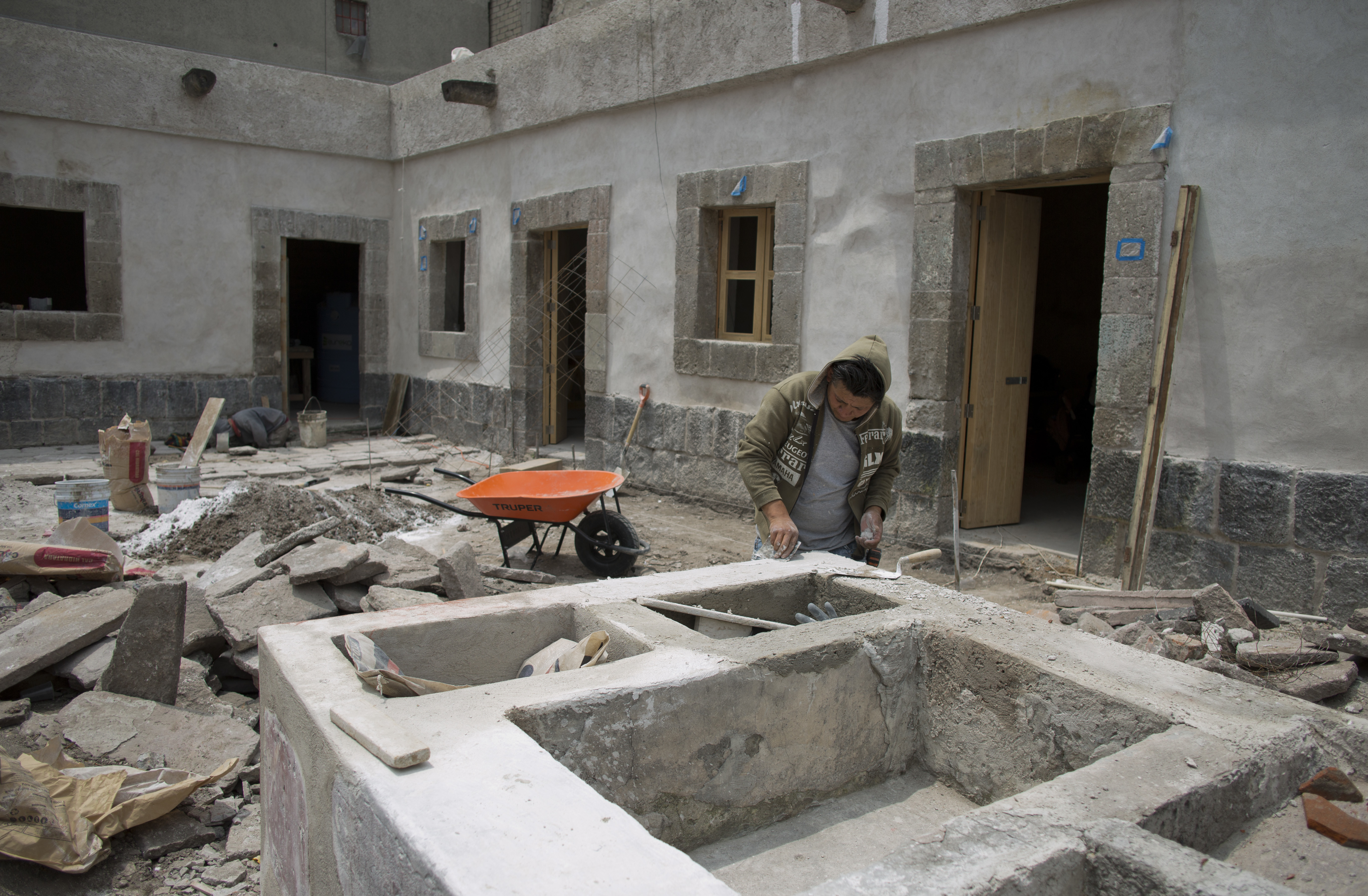 A worker restores a stone wash basin that for centuries was used to store water and for cleaning clothes, in the courtyard of 25 Manzanares Street, in Mexico City, Sept. 10, 2018.