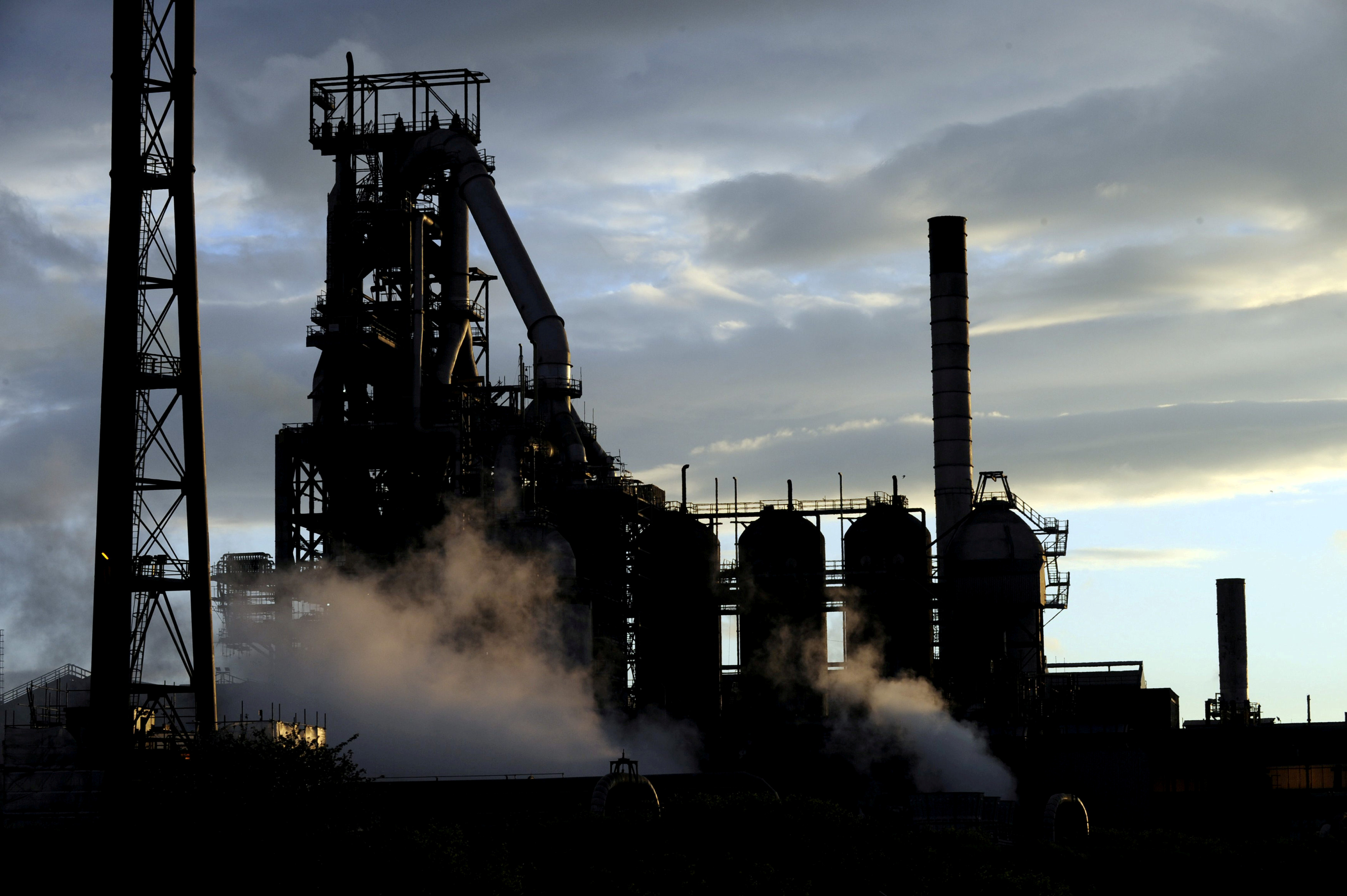 FILE - One of the blast furnaces of the Tata Steel plant is seen at sunset in Port Talbot, South Wales, May 31, 2013.