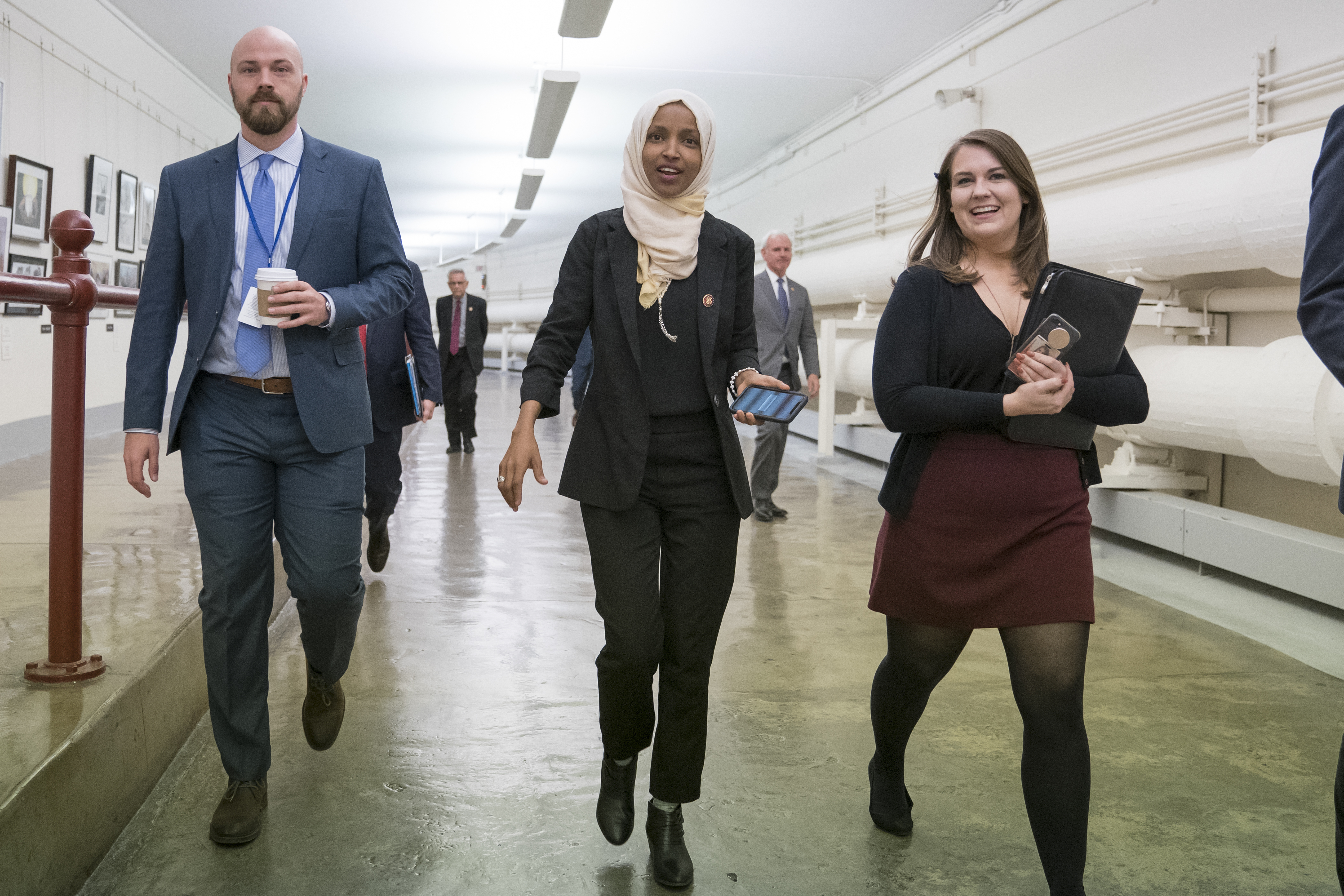 """Rep. Ilhan Omar, D-Minn., walks to the chamber, March 7, 2019, on Capitol Hill in Washington, as the House was preparing to vote on a resolution to speak out against, as Speaker of the House Nancy Pelosi said, """"anti-Semitism, anti-Islamophobia, anti-..."""
