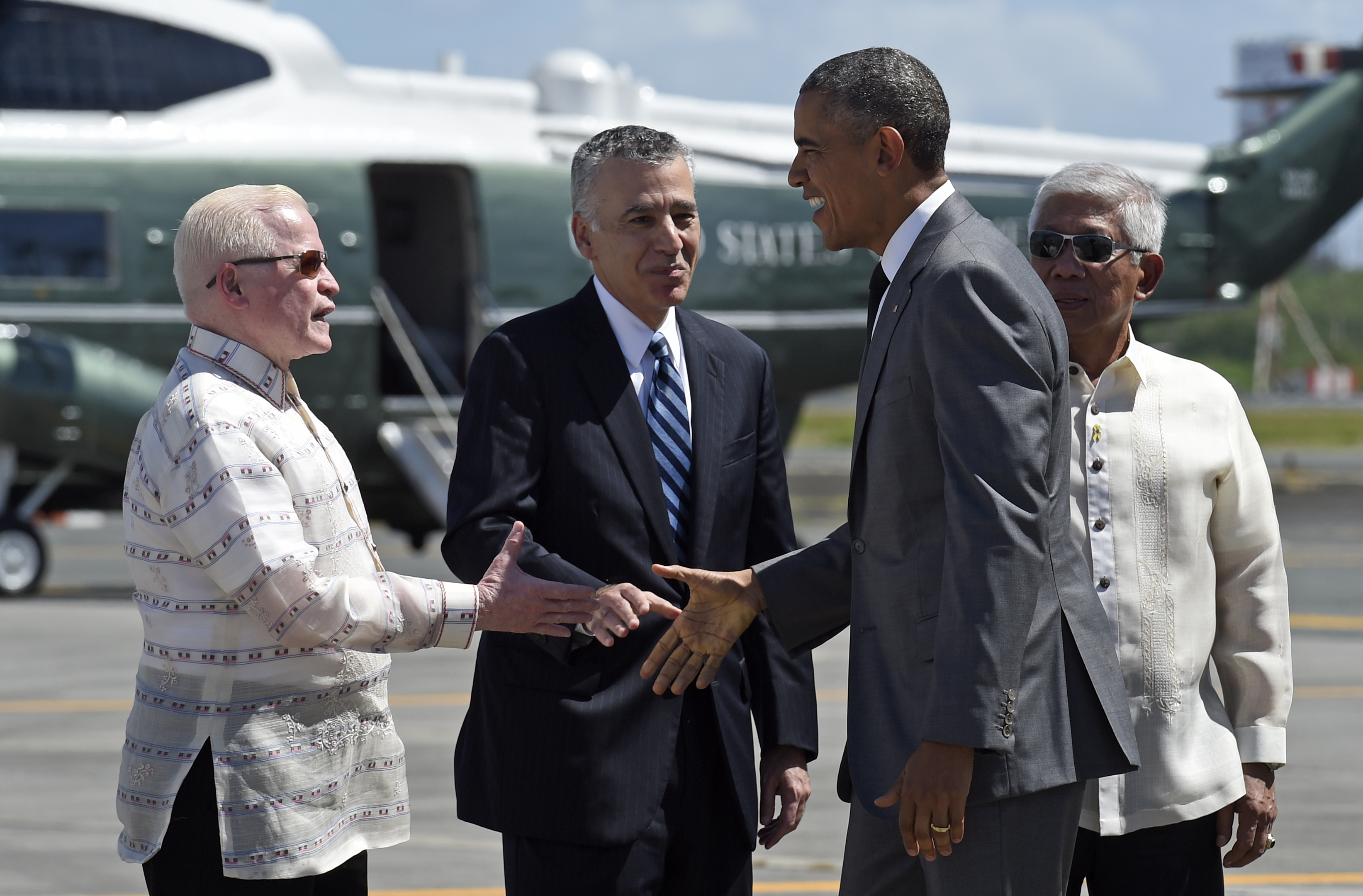 U.S. President Barack Obama, second from right, reaches to shake hands with Philippine Ambassador to the U.S. Jose Cuisia Jr., left, after arriving at Ninoy Aquino International Airport in Manila, Philippines, Nov. 17, 2015.