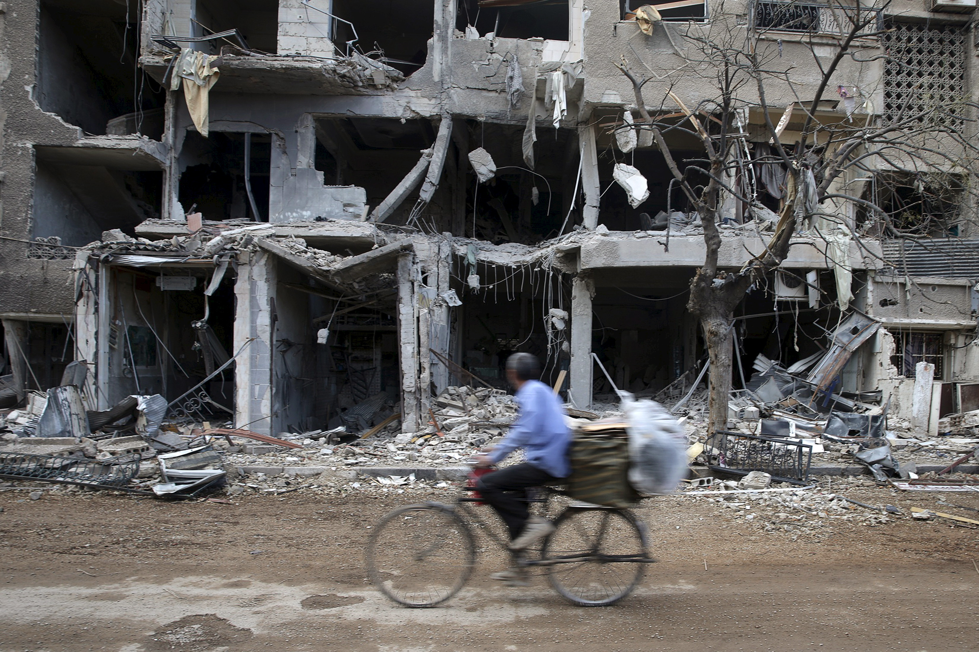 A man rides a bicycle near damaged buildings in Jobar, a suburb of Damascus, Syria, Oct. 27, 2015.