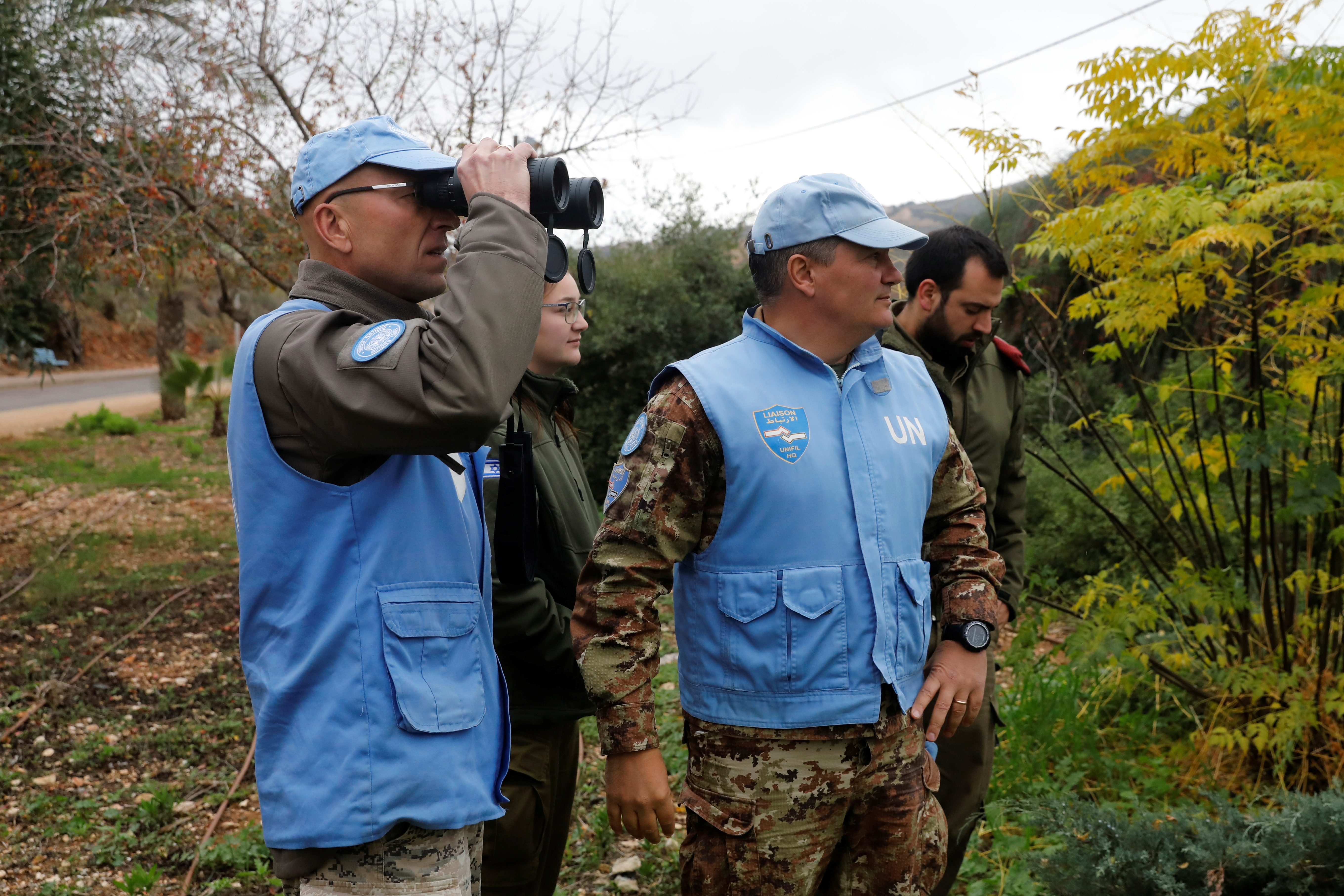 """U.N. peacekeepers and Israeli soldiers look towards the border with Lebanon the morning after the Israeli military said it had launched an operation to """"expose and thwart"""" cross-border attack tunnels from Lebanon, in Israel's northernmost town Metula..."""