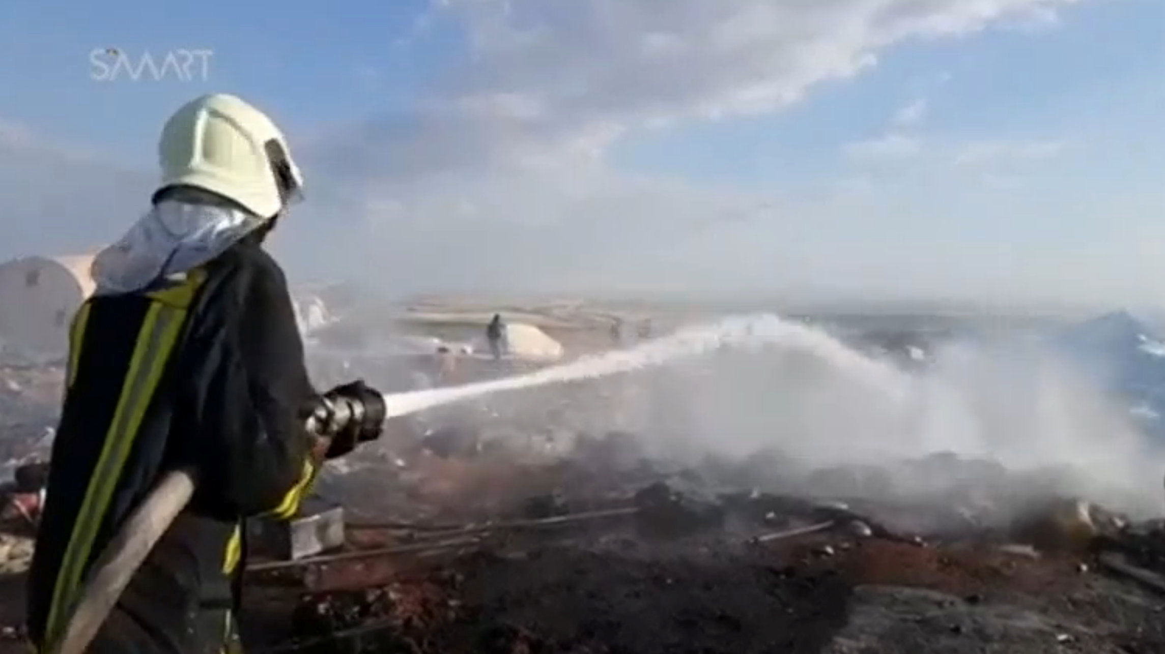 A fireman douses fire at burnt tents in a camp for internally displaced people near Sarmada in Syria's Idlib province in this undated still image taken from video on May 6, 2016.