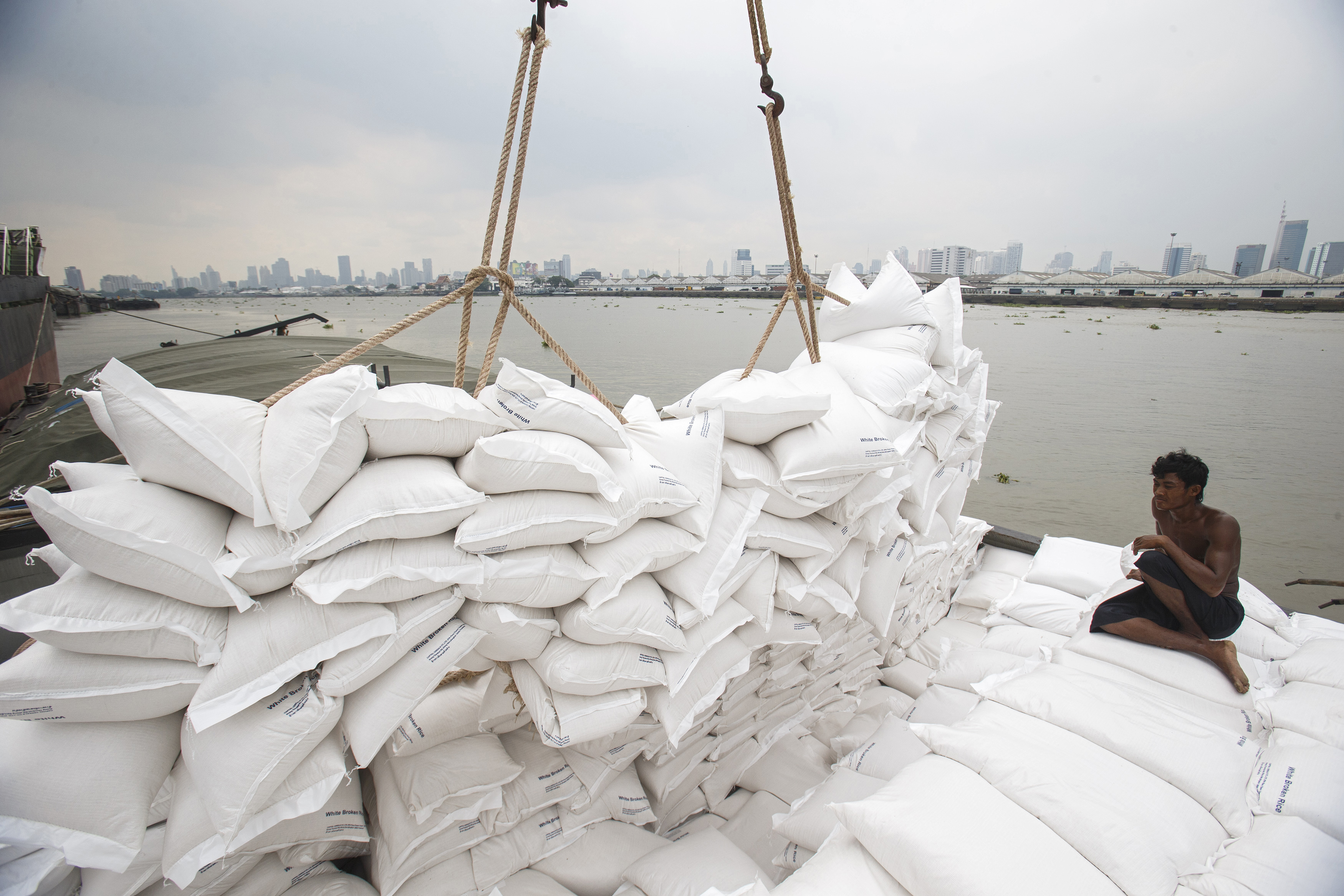 A migrant worker unloads sacks of rice from a barge to a cargo ship on The Chao Phraya River in Bangkok, Thailand, Aug. 27, 2014.