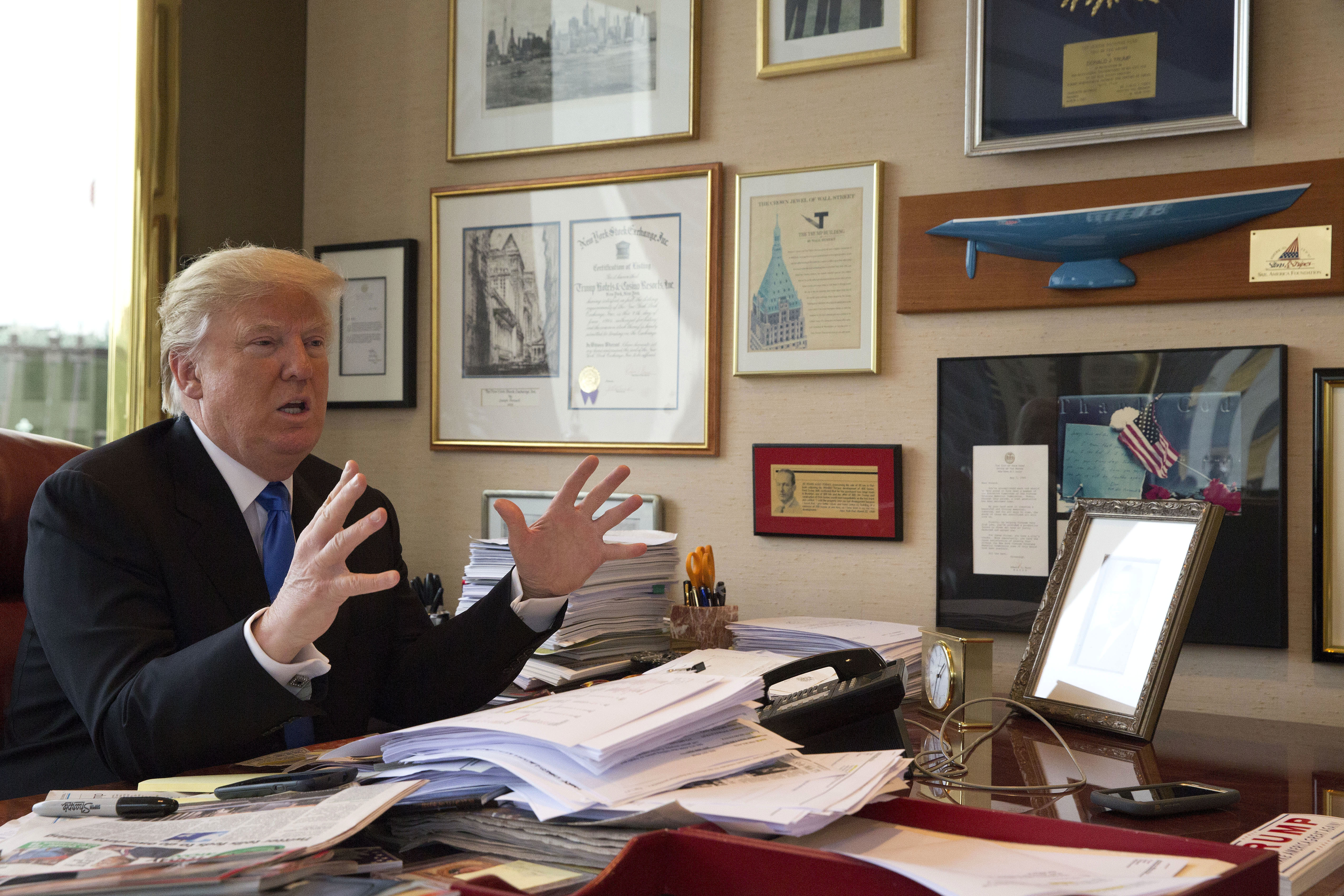 FILE - Republican presidential candidate Donald Trump gestures as he speaks during an interview with The Associated Press in his office at Trump Tower in New York, May 10, 2016. Trump once hired a man convicted of trying to break a triple murderer ou...