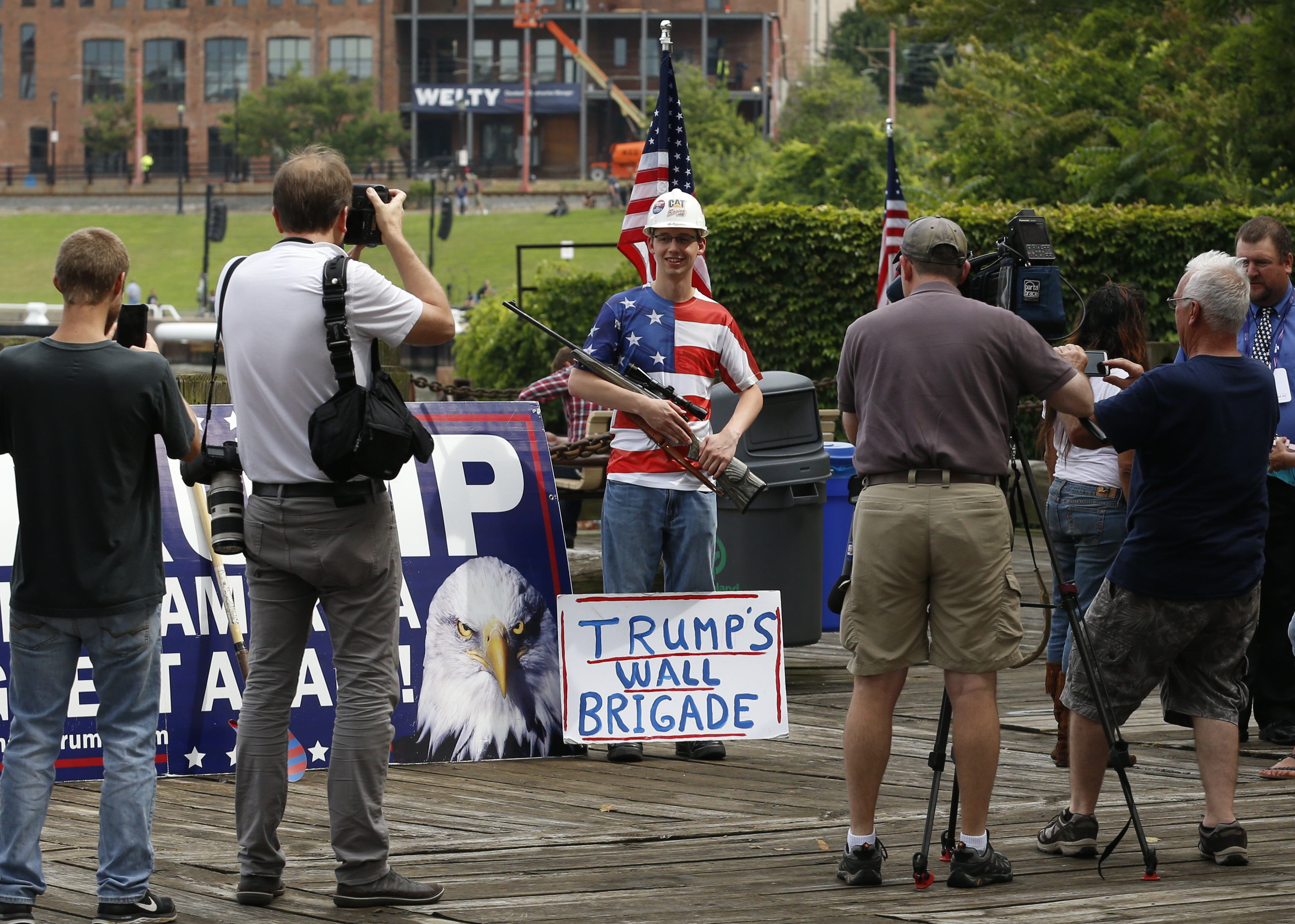 A supporter of Republican presidential candidate Donald Trump poses with a rifle while waiting for a pro-Trump rally to begin near the Republican National Convention in Cleveland, Ohio, July 18, 2016.