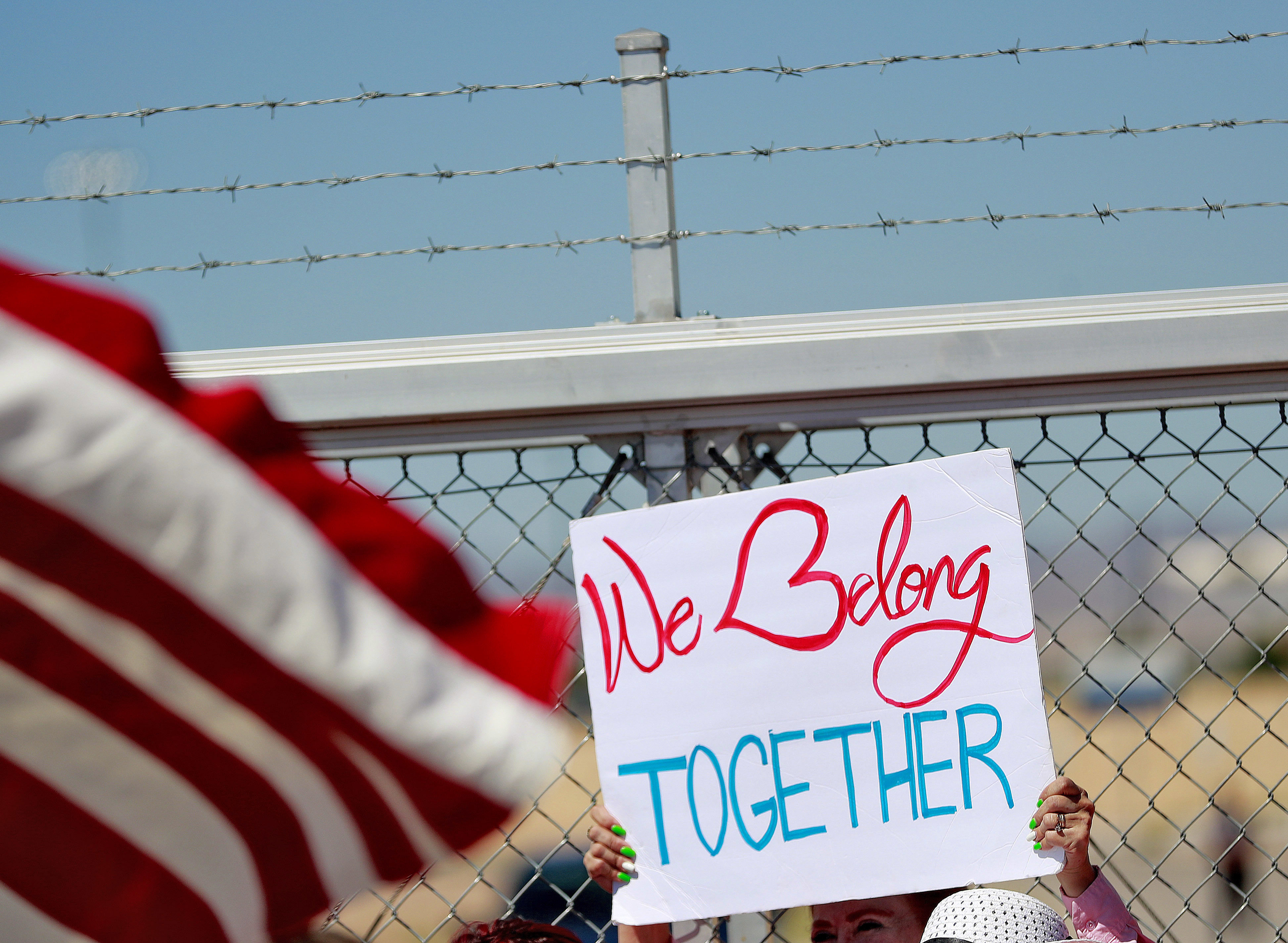 A protester holds a sign outside a closed gate at the Port of Entry facility, June 21, 2018, in Fabens, Texas, where tent shelters are being used to house separated family members.