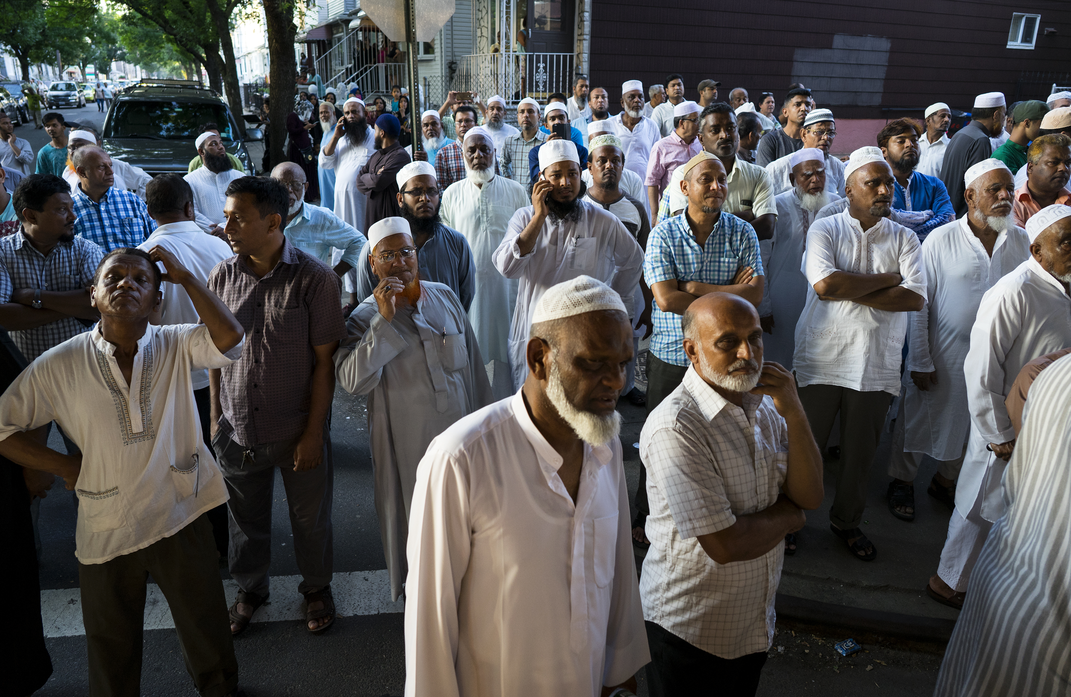 In this Saturday, Aug. 13, 2016, photo, people gather near a crime scene for a demonstration after the leader of a New York City mosque and an associate were fatally shot in a brazen daylight attack as they left afternoon prayers Saturday.