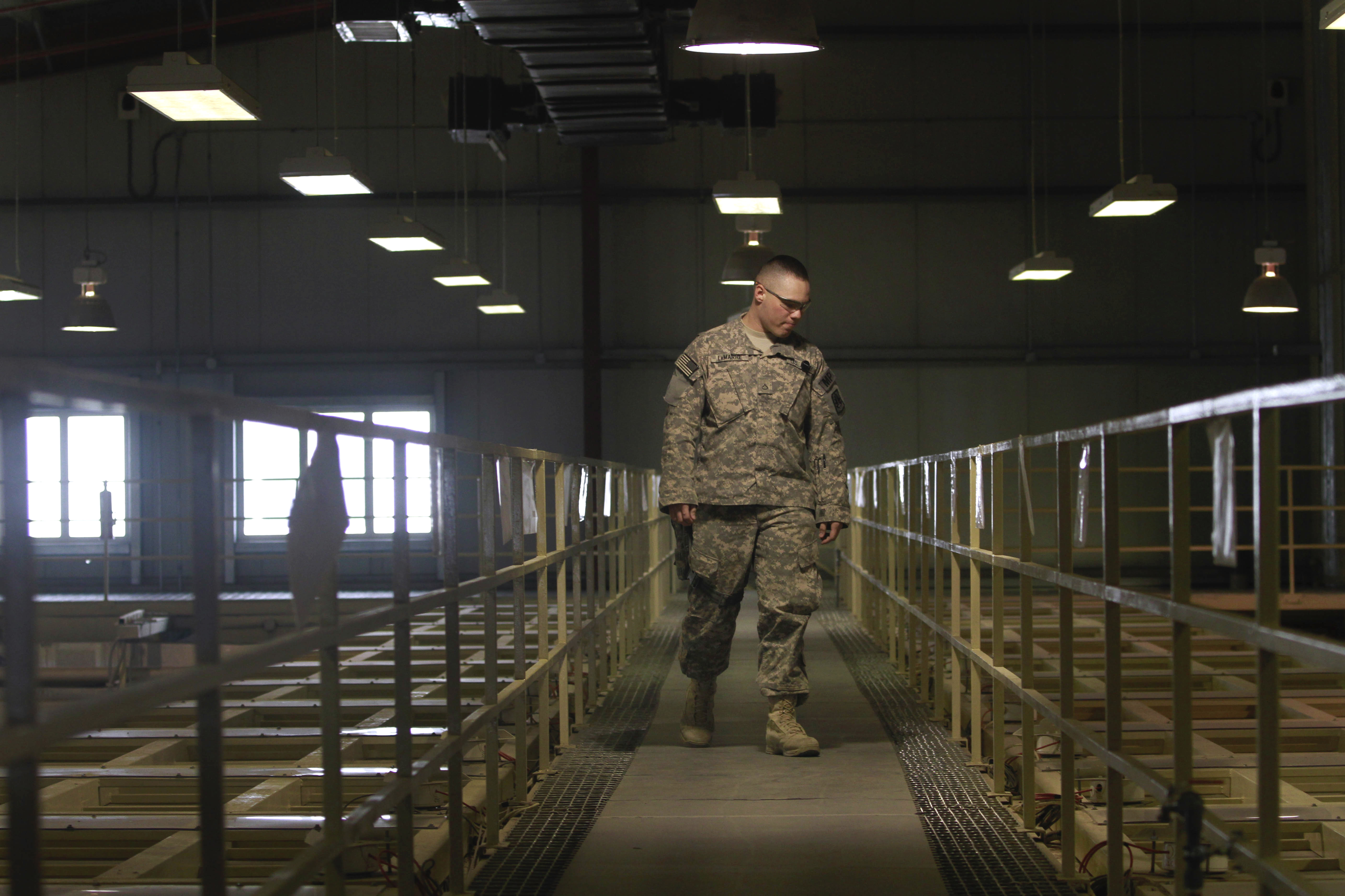 FILE - A U.S. military guard watches over detainee cells inside the Parwan detention facility near Bagram Air Field in Afghanistan, March 23, 2011. The Pentagon has denied operating secret jails in Afghanistan, although human rights groups and former...