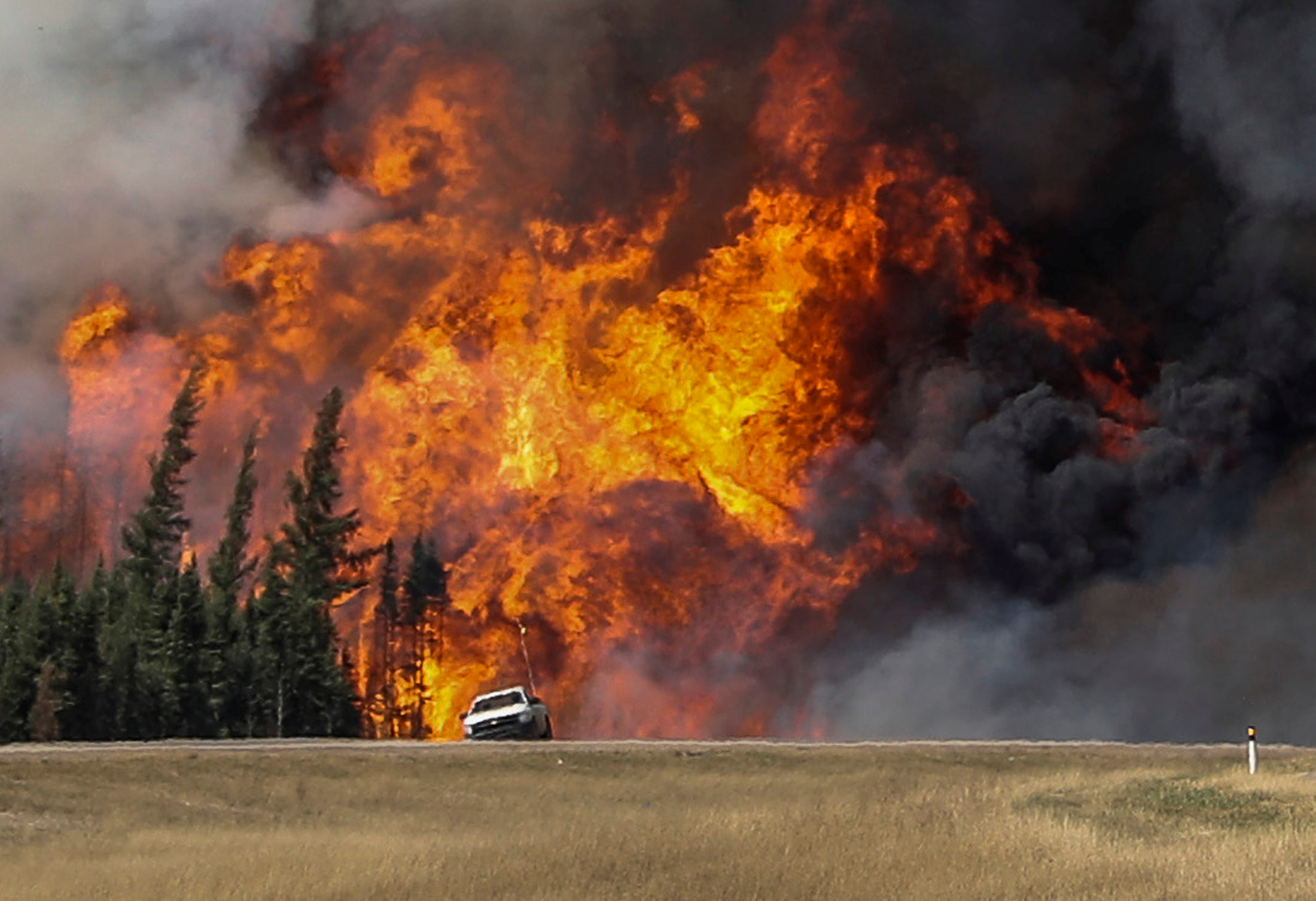 Smoke and flames from the wildfires erupt behind a car on the highway near Fort McMurray, Alberta, Canada, May 7, 2016.