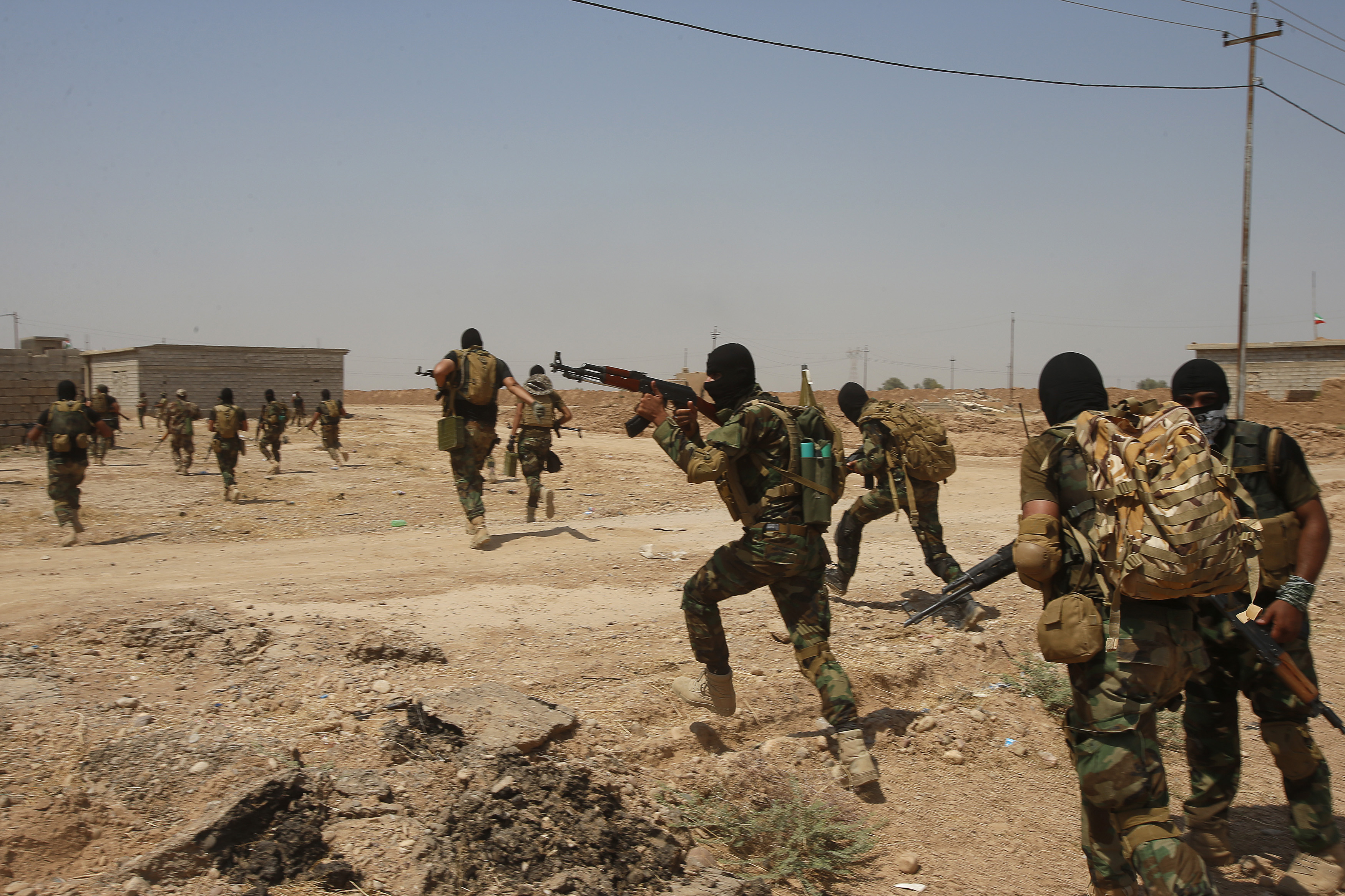 Asaib Ahl al-Haq Shi'ite militia fighters from the south of Iraq run during a mission to take control of Sulaiman Pek village from Islamist State militants, in the northwest of Tikrit city, Sept. 1, 2014.