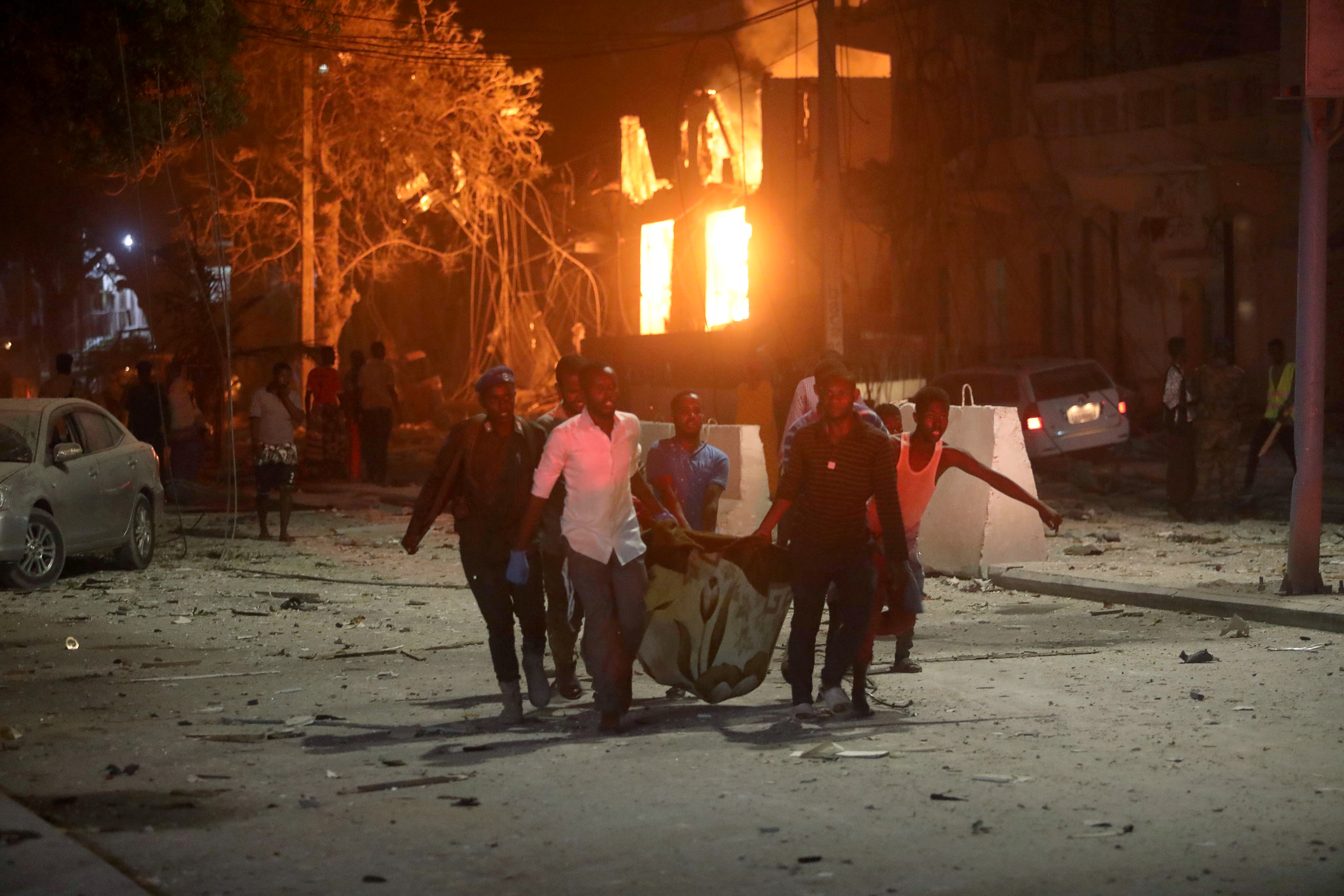 Rescue workers evacuate an injured man from the scene where a suicide car bomb exploded targeting a Mogadishu hotel in a business center at Maka Al Mukaram street in Mogadishu, Somalia. Feb. 28, 2019.