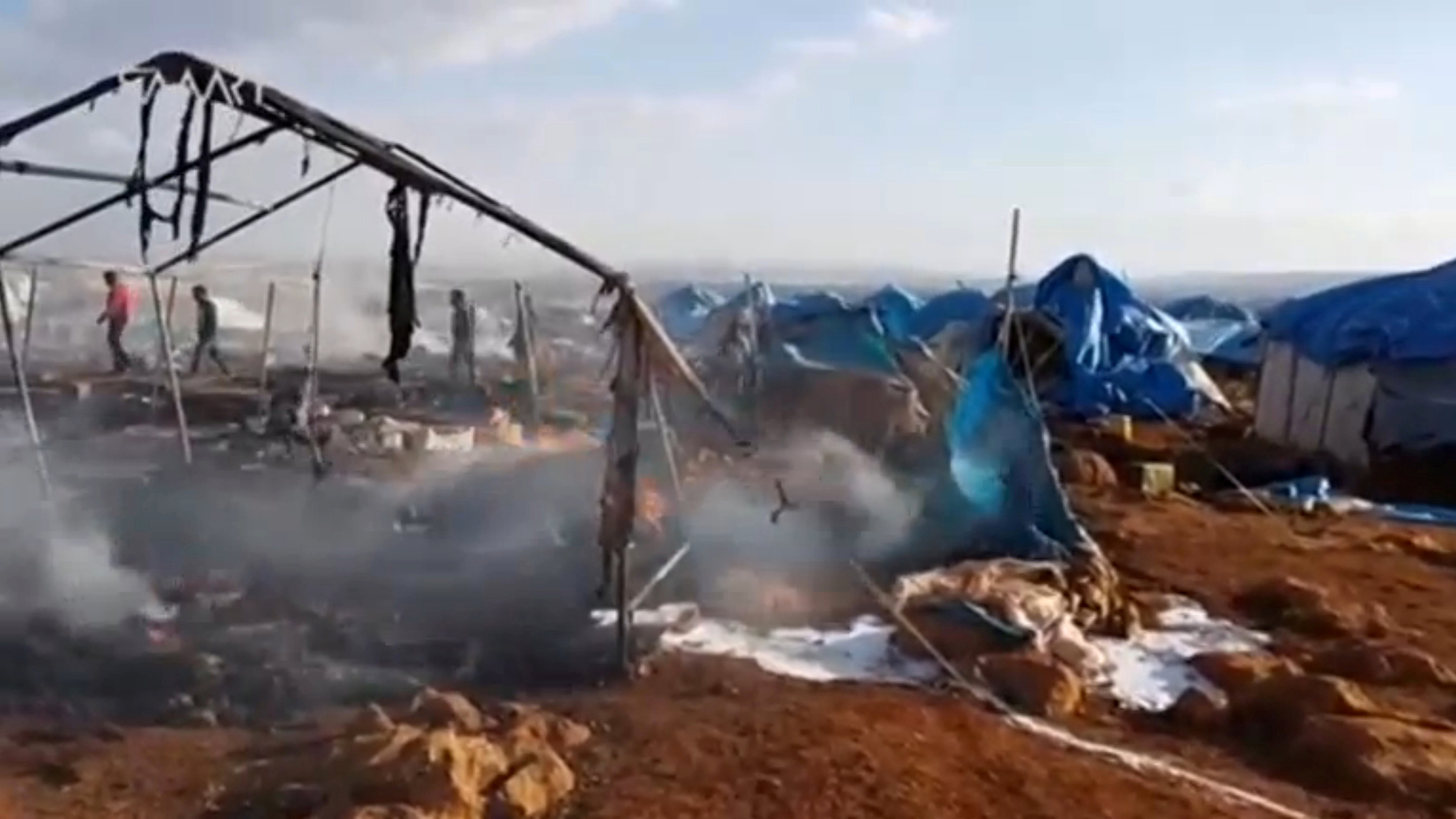 People walk though burnt tents at a camp for internally displaced people near Sarmada in Syria's Idlib province in this undated still image taken from video on May 6, 2016.