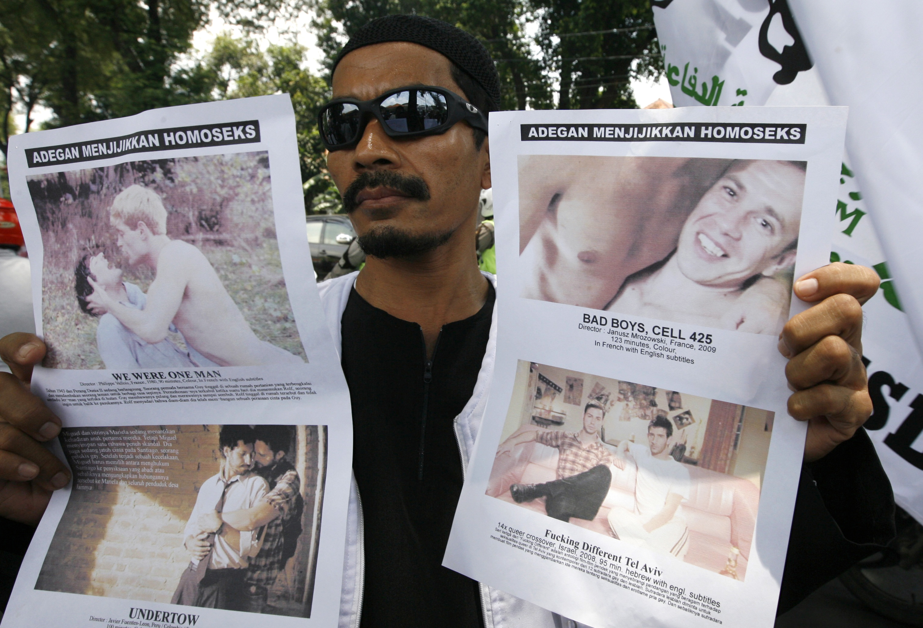 A member of the Islamic Defenders Front (FPI) holds up posters protesting against films screened at the Q! Film Festival during a protest in front of GoetheHaus in Jakarta, Sep. 28, 2010. The gay and lesbian community in Indonesia has been facing dis...