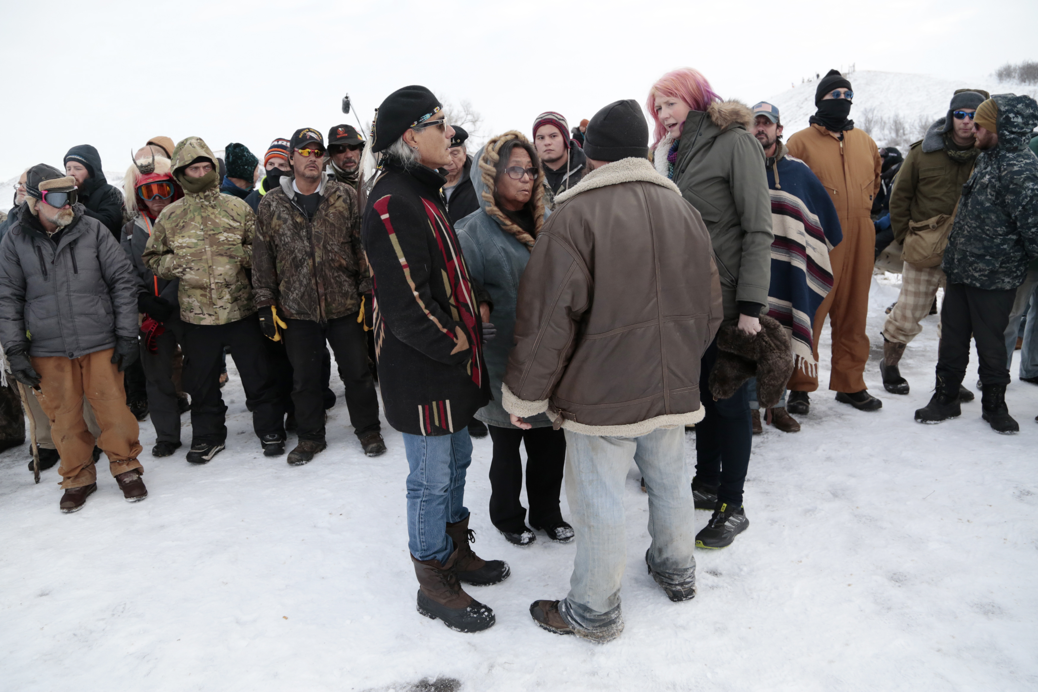 Phyllis Young, center, of the Standing Rock Sioux Tribe talks with veterans who oppose the Dakota Access oil pipeline on Backwater Bridge near Cannon Ball, N.D., Dec. 2, 2016.