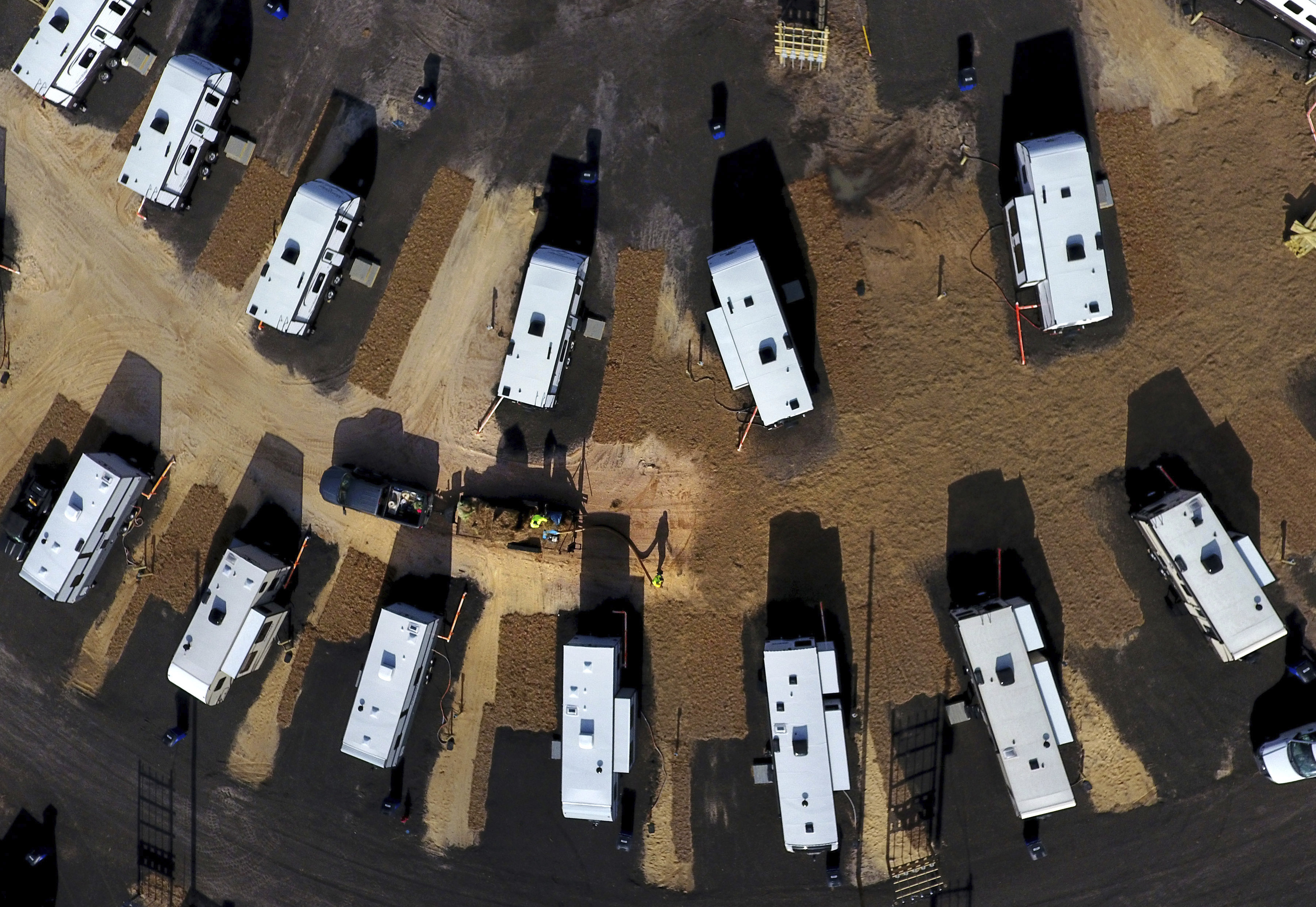 A worker sprays straw around newly setup Federal Emergency Management Agency trailers for residents left homeless by Hurricane Michael in Panama City, Fla, Thursday, Jan. 24, 2019.