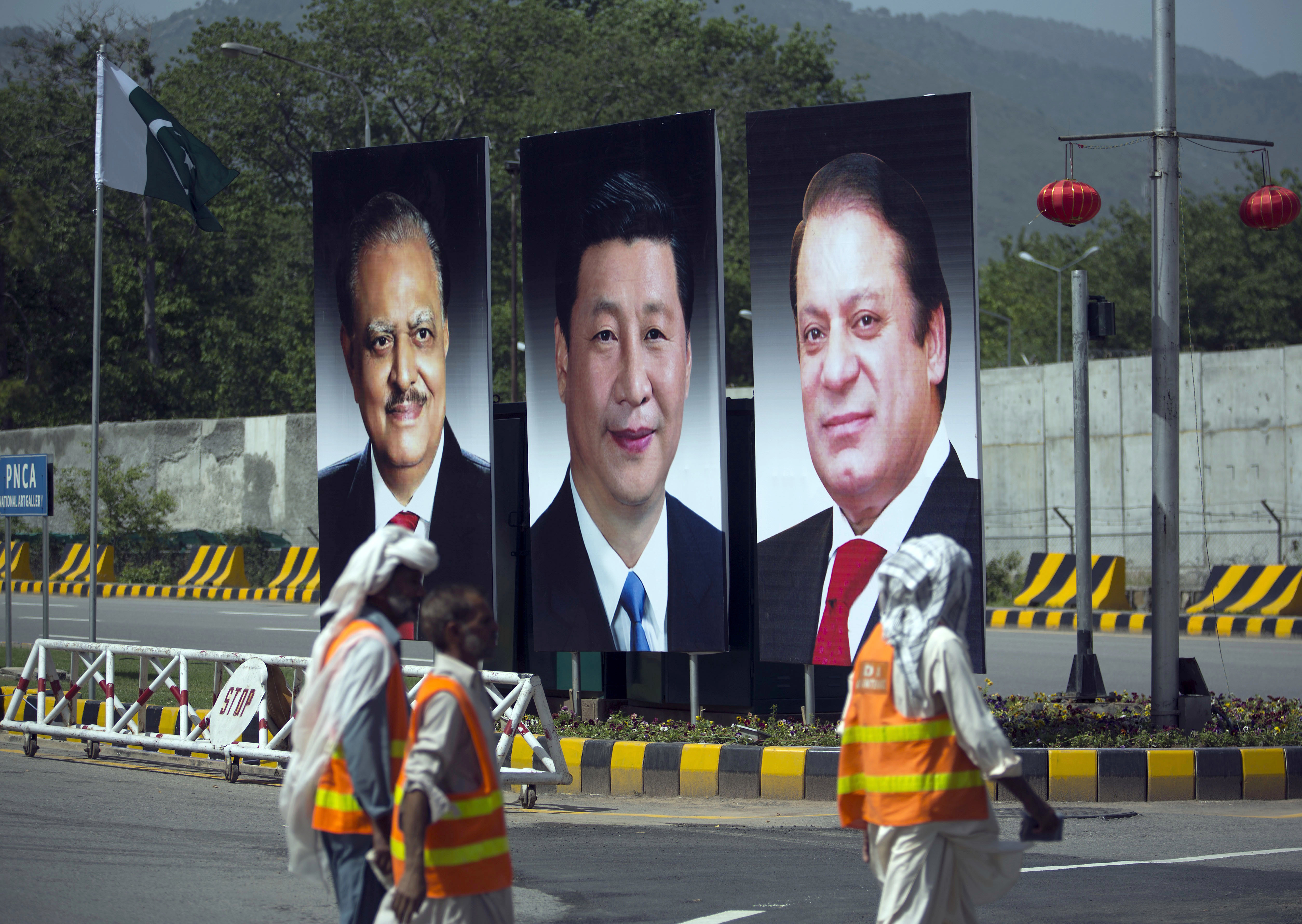 FILE - Municipality workers walk past a billboard showing pictures of Chinese President Xi Jinping, center, with Pakistan's President Mamnoon Hussain, left, and Prime Minister Nawaz Sharif on display during a two-day visit by the Chinese president, A...