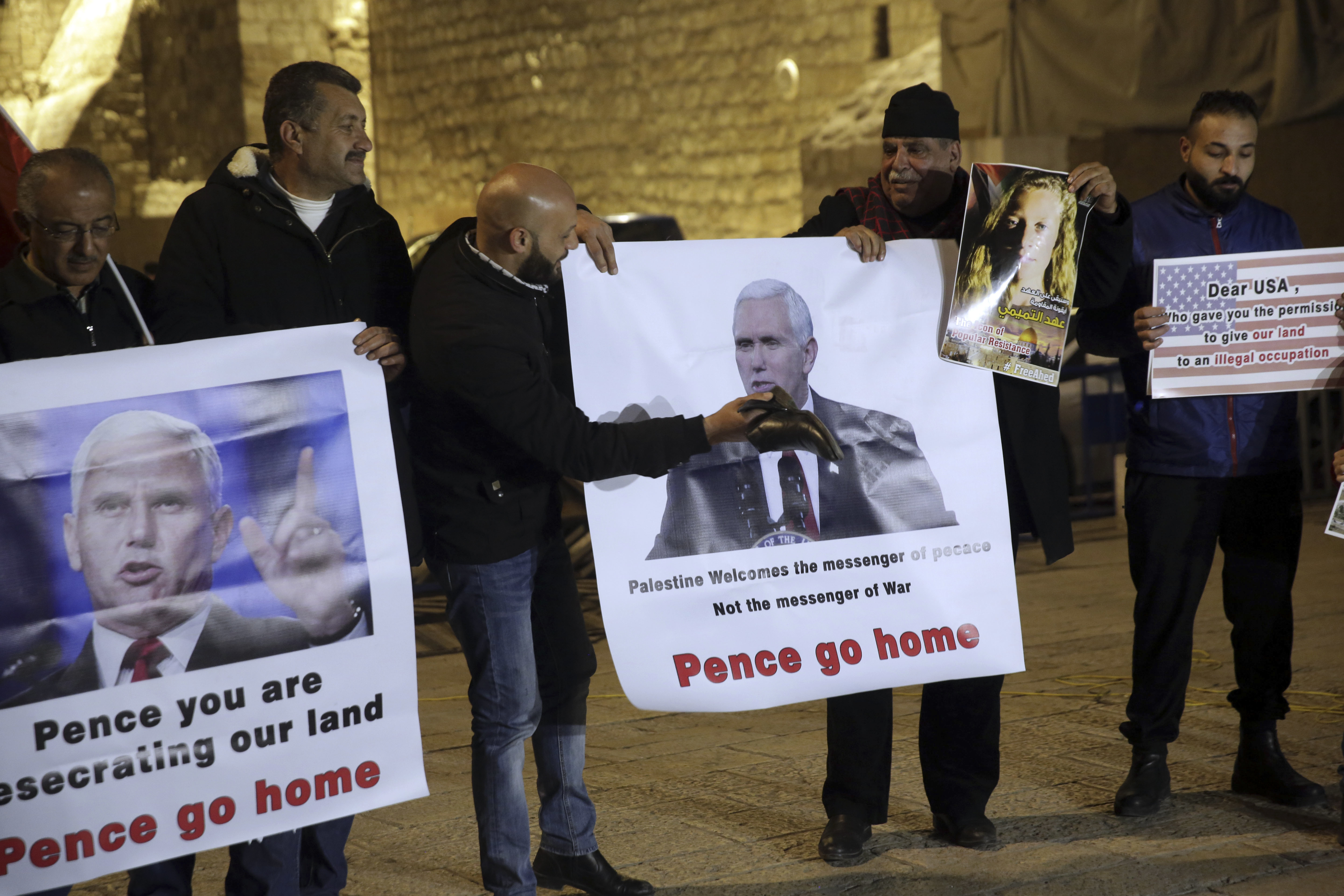Palestinians hold posters of U.S. President Mike Pence as they protest his visit to Israel in Bethlehem, West Bank, Sunday, Jan. 21, 2018.