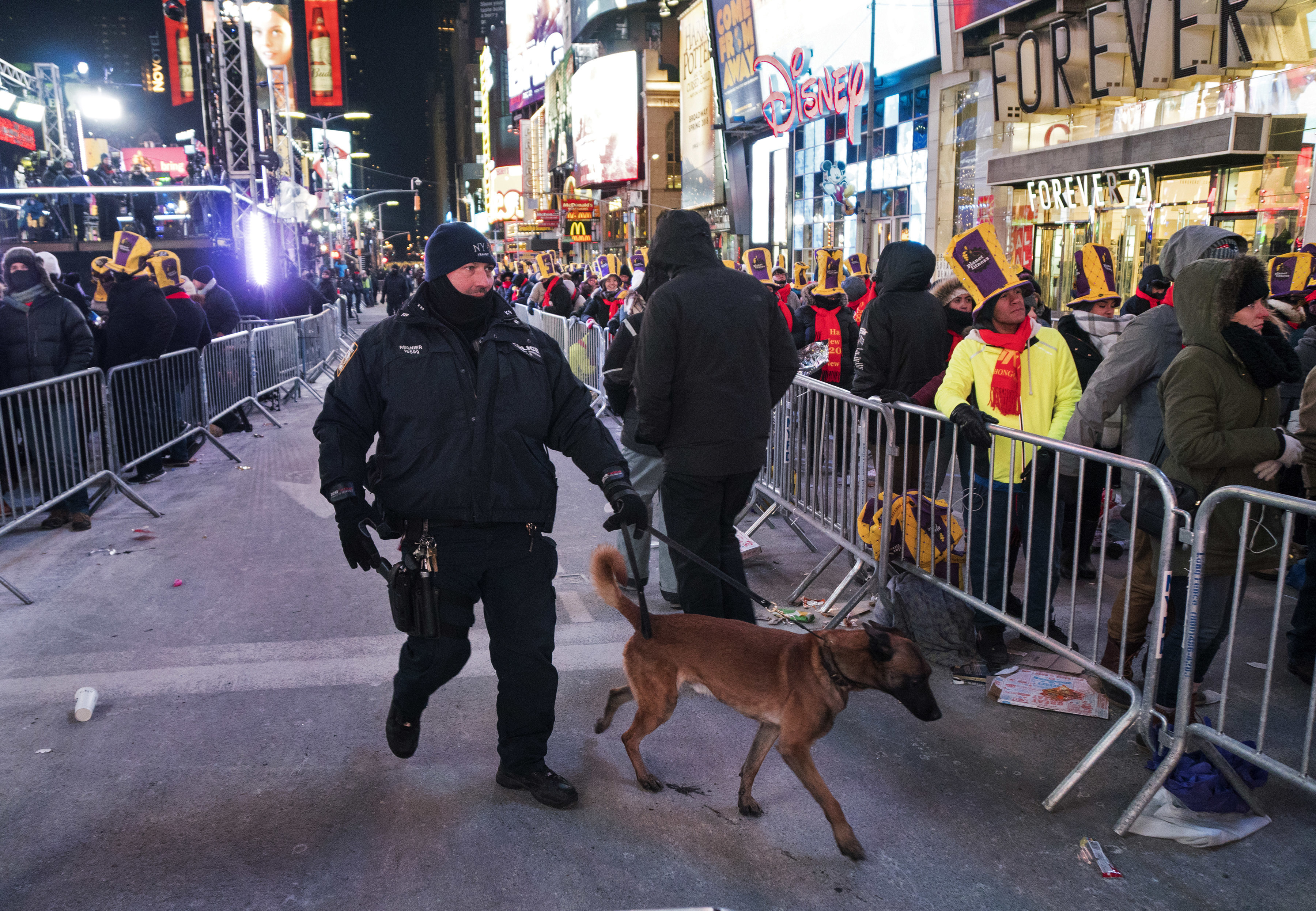 A New York City canine police officer walks past revelers gathered on Times Square in New York, Dec. 31, 2017.