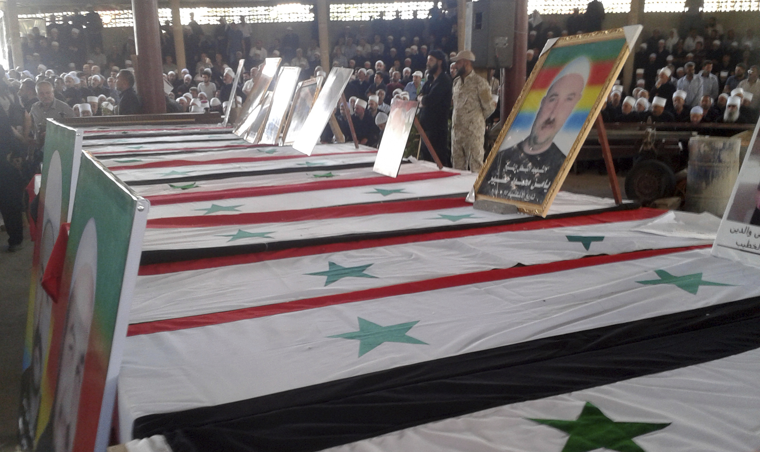 Photo released by the Syrian official news agency SANA shows mourners at a mass funeral of people killed a day earlier by a series of suicide bombings launched by the Islamic State's fighters on the eastern and northern countryside of the southern pr...