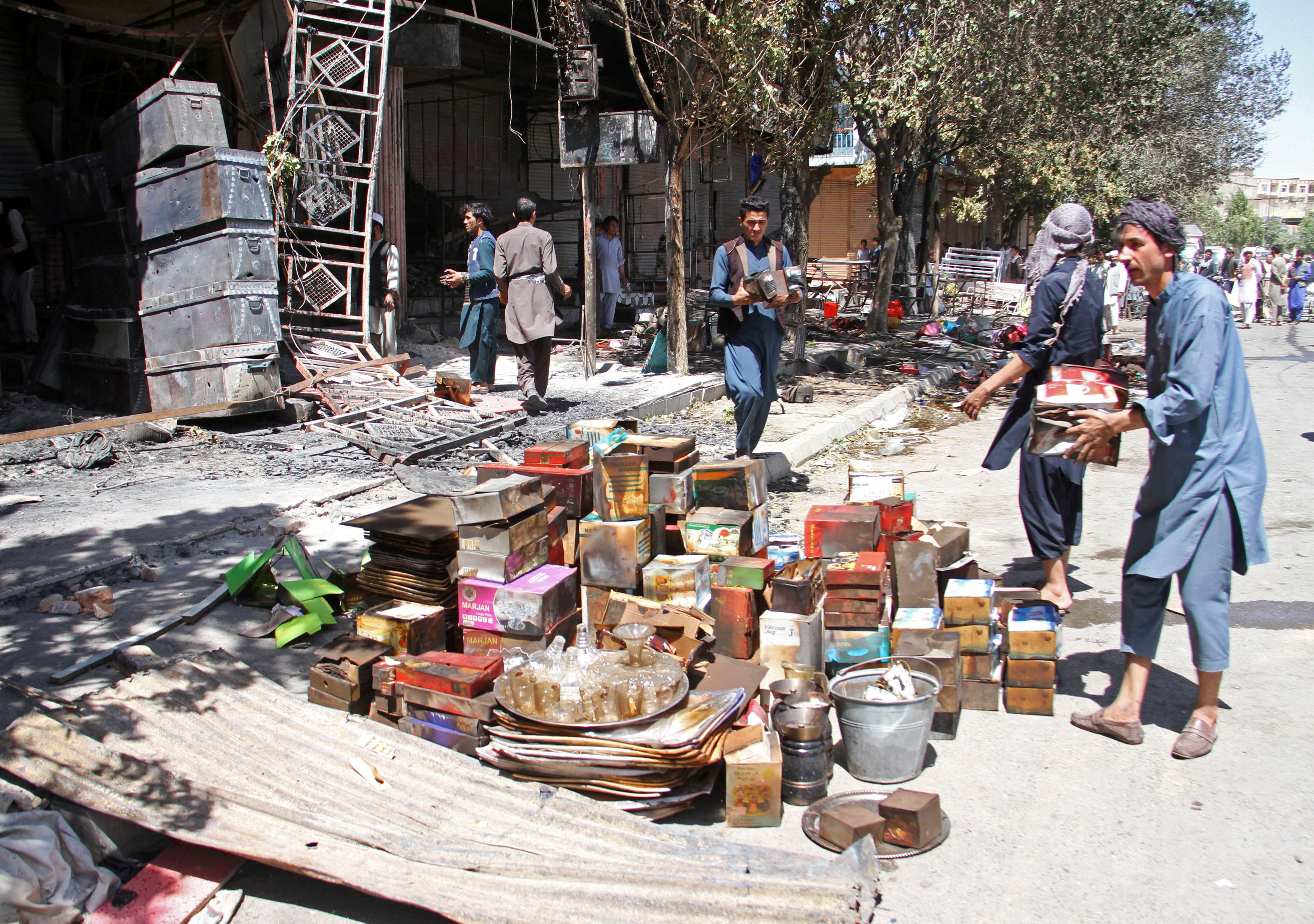 Afghan shopkeepers try to recover items from burning shops after a Taliban attack in Ghazni city, Afghanistan, Aug. 14, 2018.