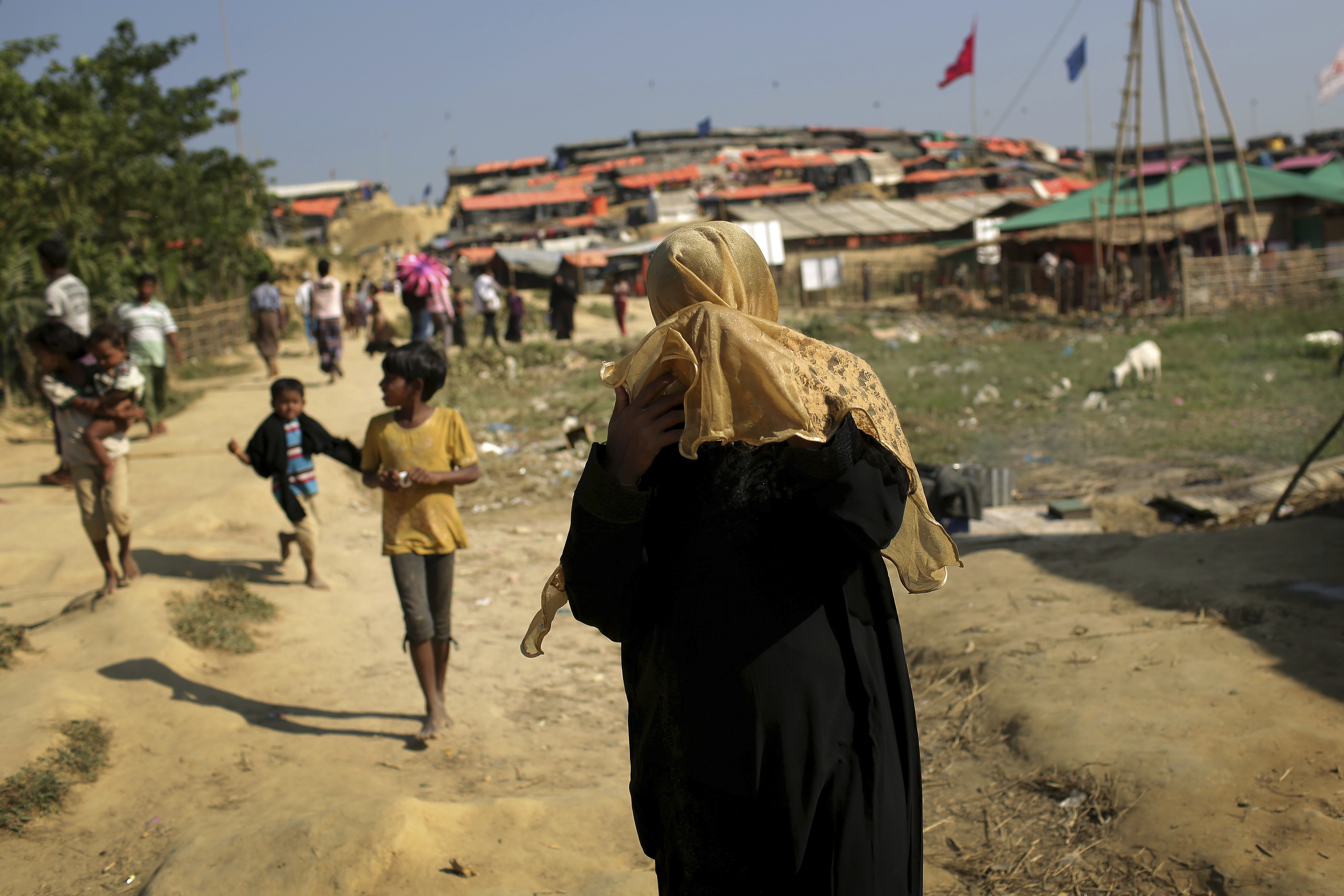 A Rohingya Muslim woman covers her face from the afternoon dust and heat as she walks through Jamtoli refugee camp, Nov. 27, 2017, in Bangladesh. Since late August, more than 630,000 Rohingya have fled Myanmar's Rakhine state into neighboring Banglad...